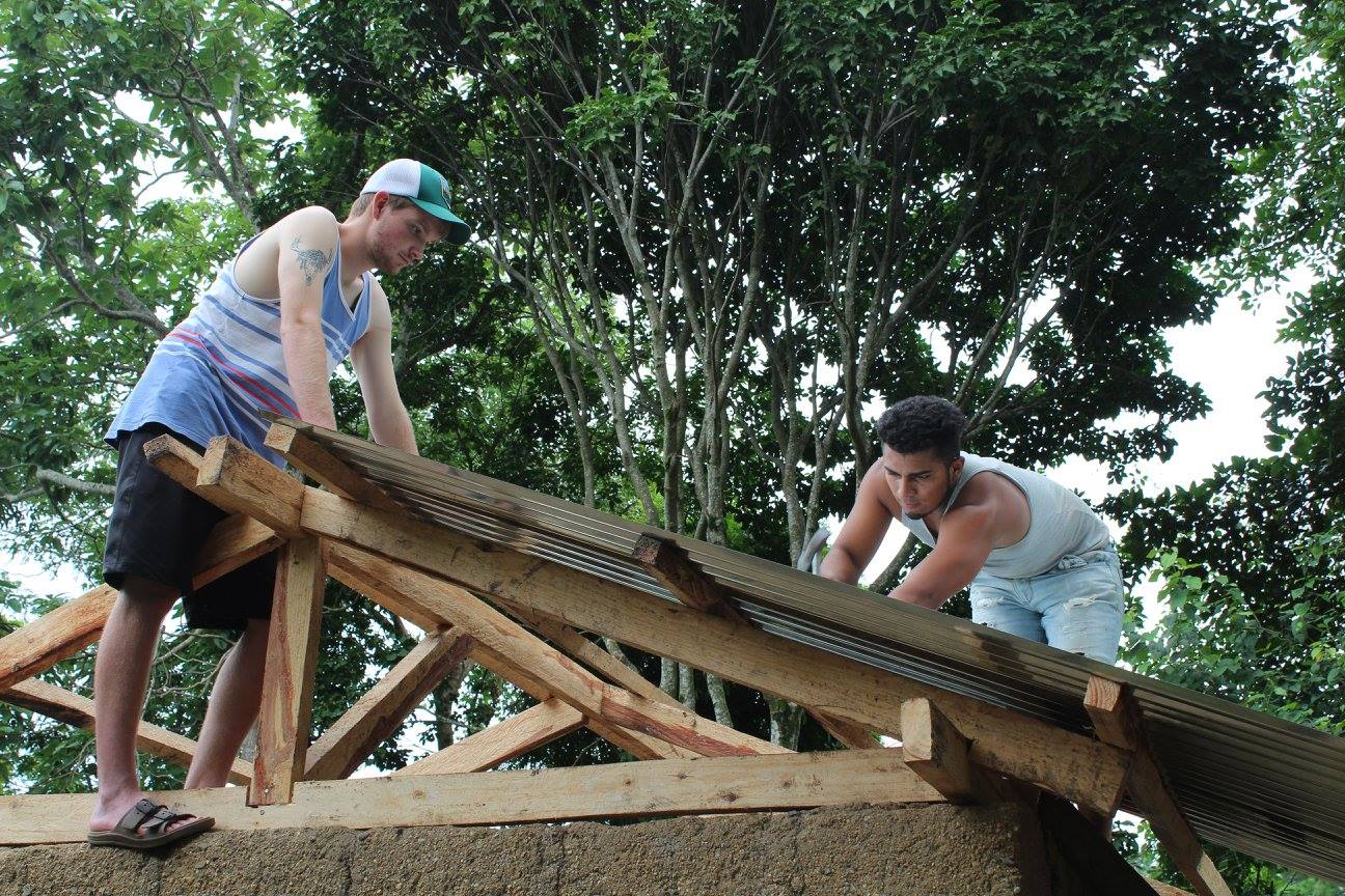 Two volunteers, one from one country and the other from another country, working side-by-side showing a Mercy familiy the love of Jesus by replacing the roof.