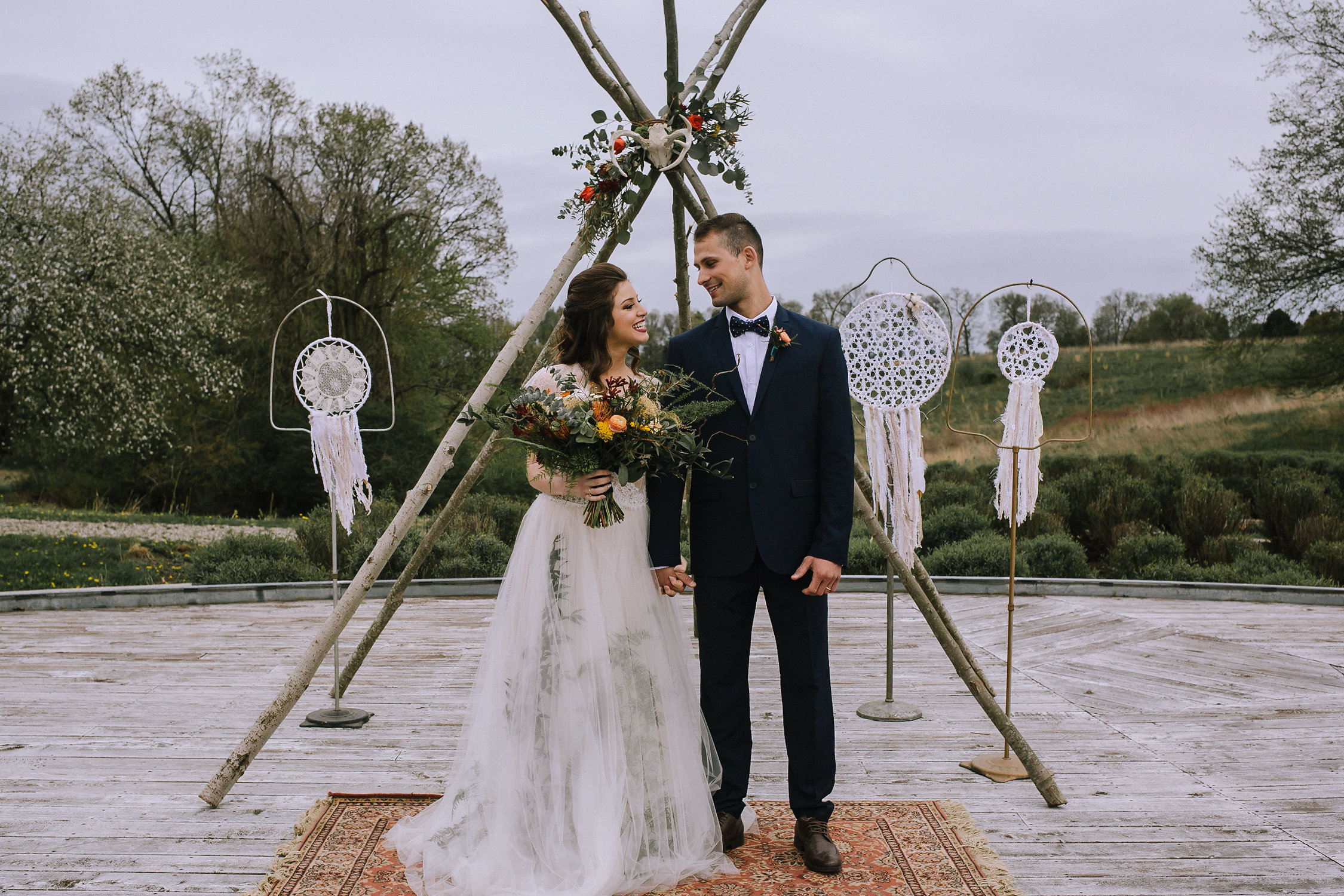 Wedding ceremony at Chatham University Eden Hall featuring a bohemian teepee, dream catchers and boho rug from Vintage Alley Rentals. Flowers by Community Flower Shop.