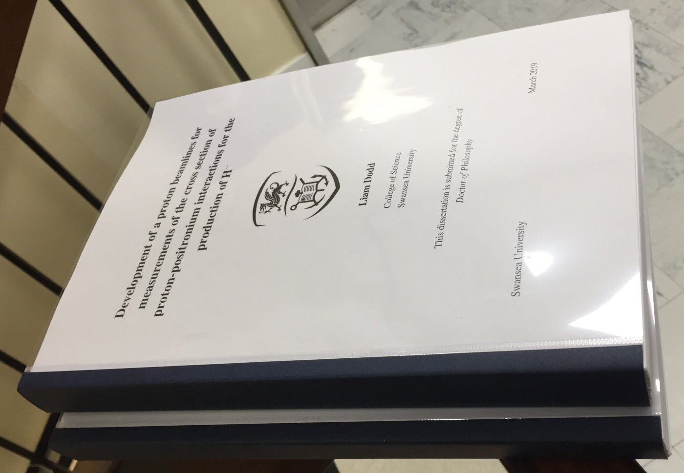 A finished thesis, balanced precariously upon a Bannister on the 6th floor of Vivian Tower.