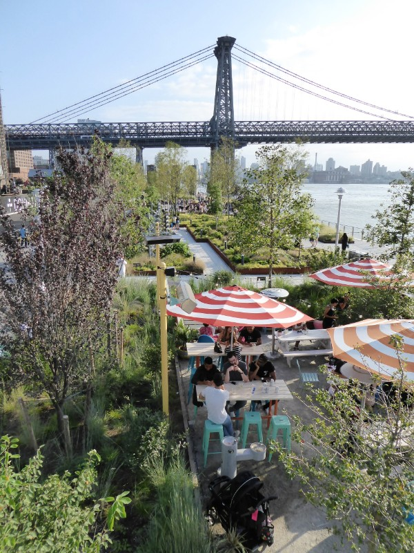 View over park  from elevated walkway with outdoor eating area & Williamsburg Bridge beyond