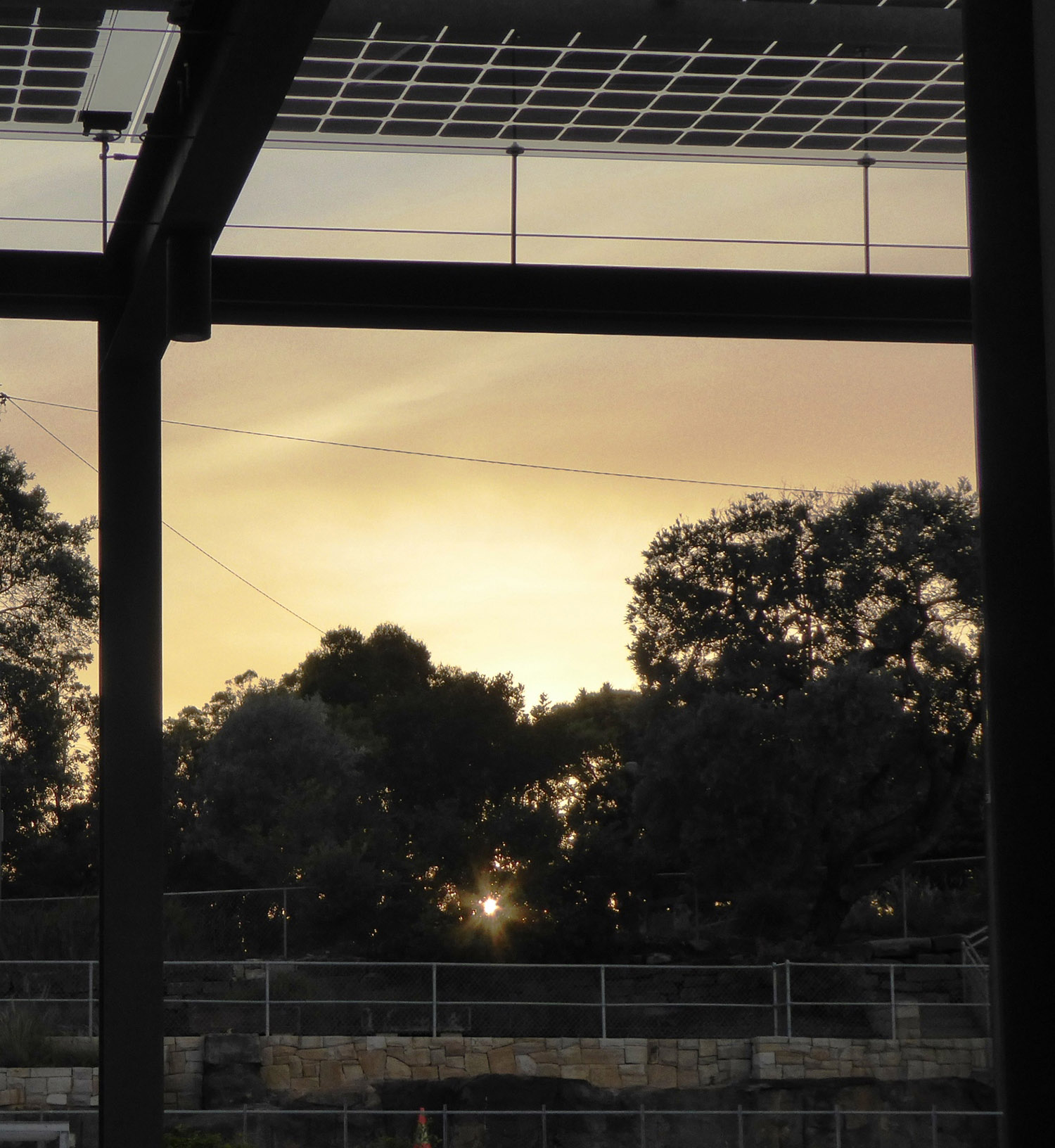 Sunrise through pergola with solar collectors