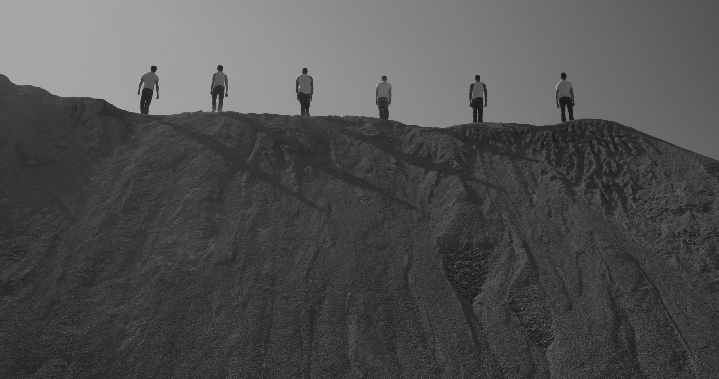 Men standing across hill.jpg