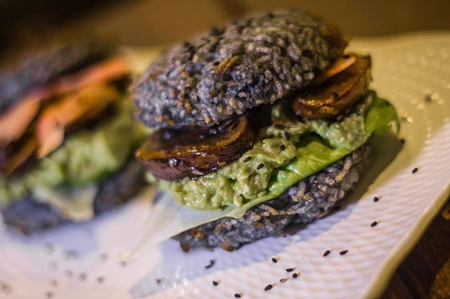No passport needed for this one. Charcoal Rice Burgers | Activated Charcoal Sticky Rice Burger layered with Wasabi Guac, Greens, Marinated Portobello, Pickled Ginger and finished with Seaweed Salad & Sesame.  Come experience a new philosophy in nightlife. #vegan #vegetarian #YXE #glutenfree #nightlife #dtnyxe #karma #plantbased