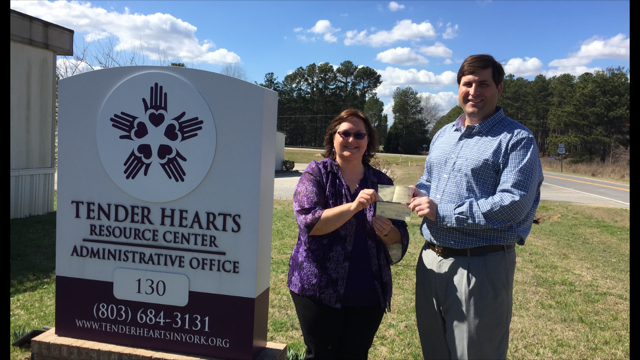 Board member and Treasurer, Derek Lewis, presents a check to Ainslee Moss, Executive Director of Tender Hearts. The check will help Tender Hearts support homeless women and children and to help them start their new homeless shelter.