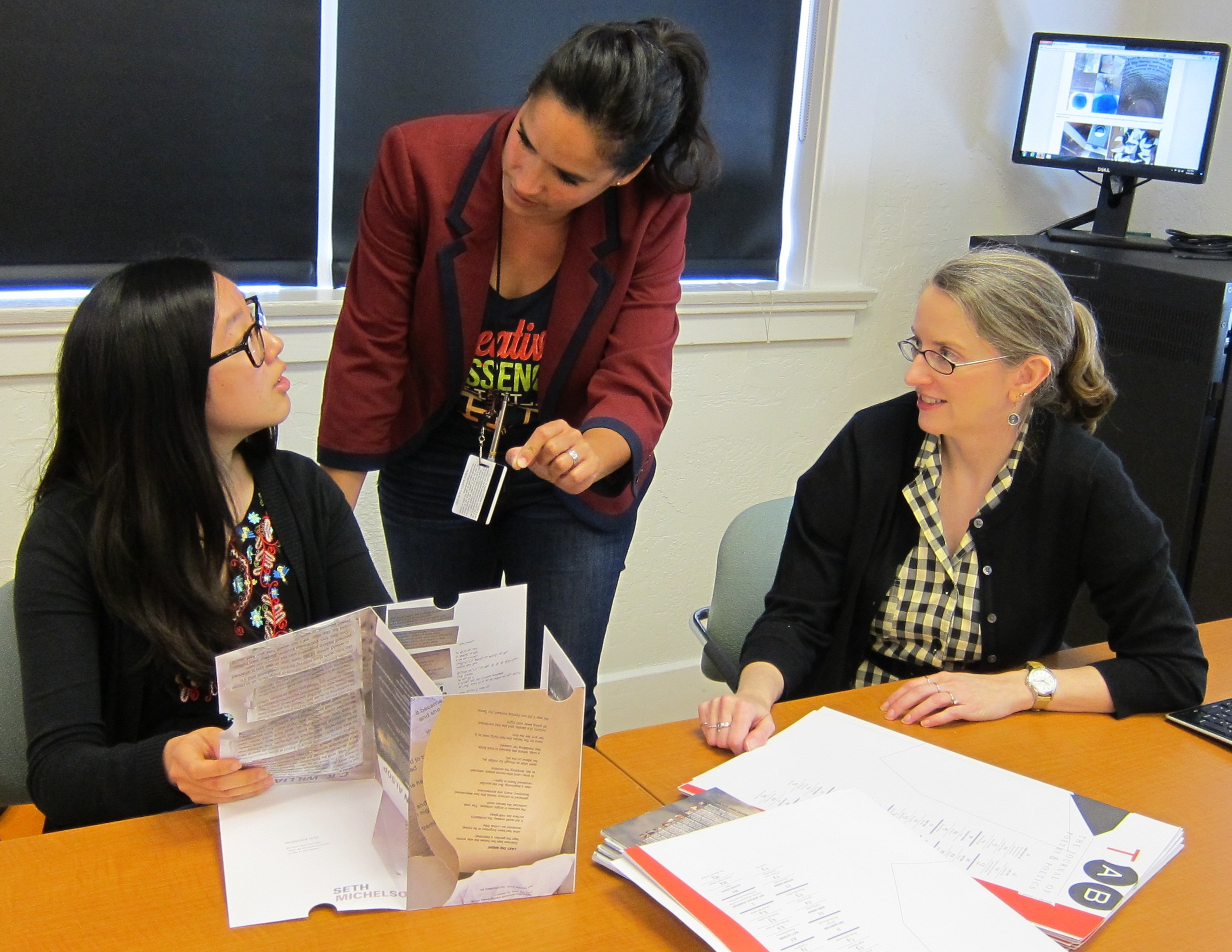 Professor of Art Claudine Jaenichen (middle) describes the interplay of time and space in  TAB: Volume Two to Audrey Chang '17 (left). Professor of English Anna Leahy, Ph.D. (right) explains how the content is selected, providing a wide range of poetic aesthetics.