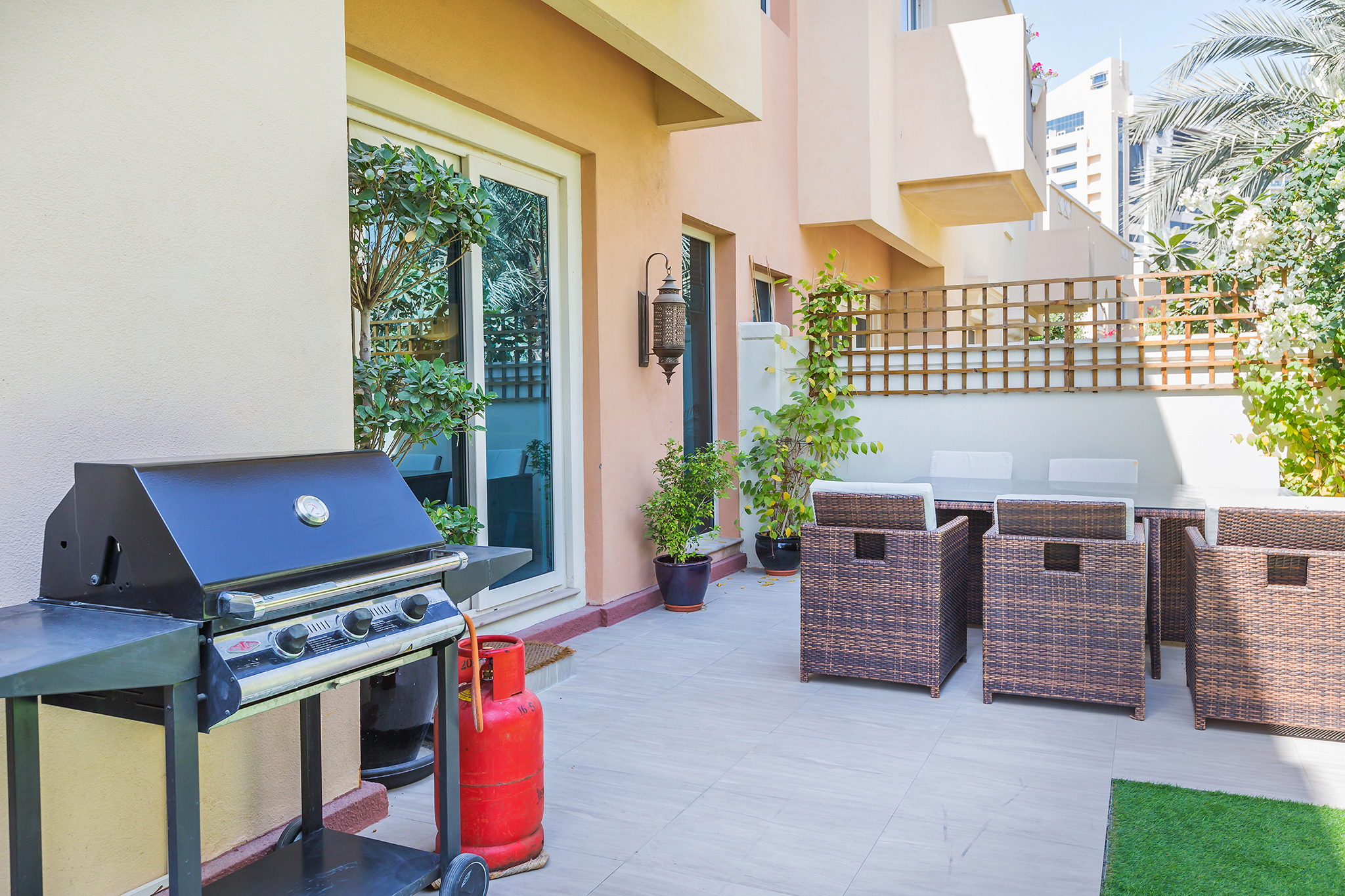 Large garden with outdoor dining table and gas BBQ
