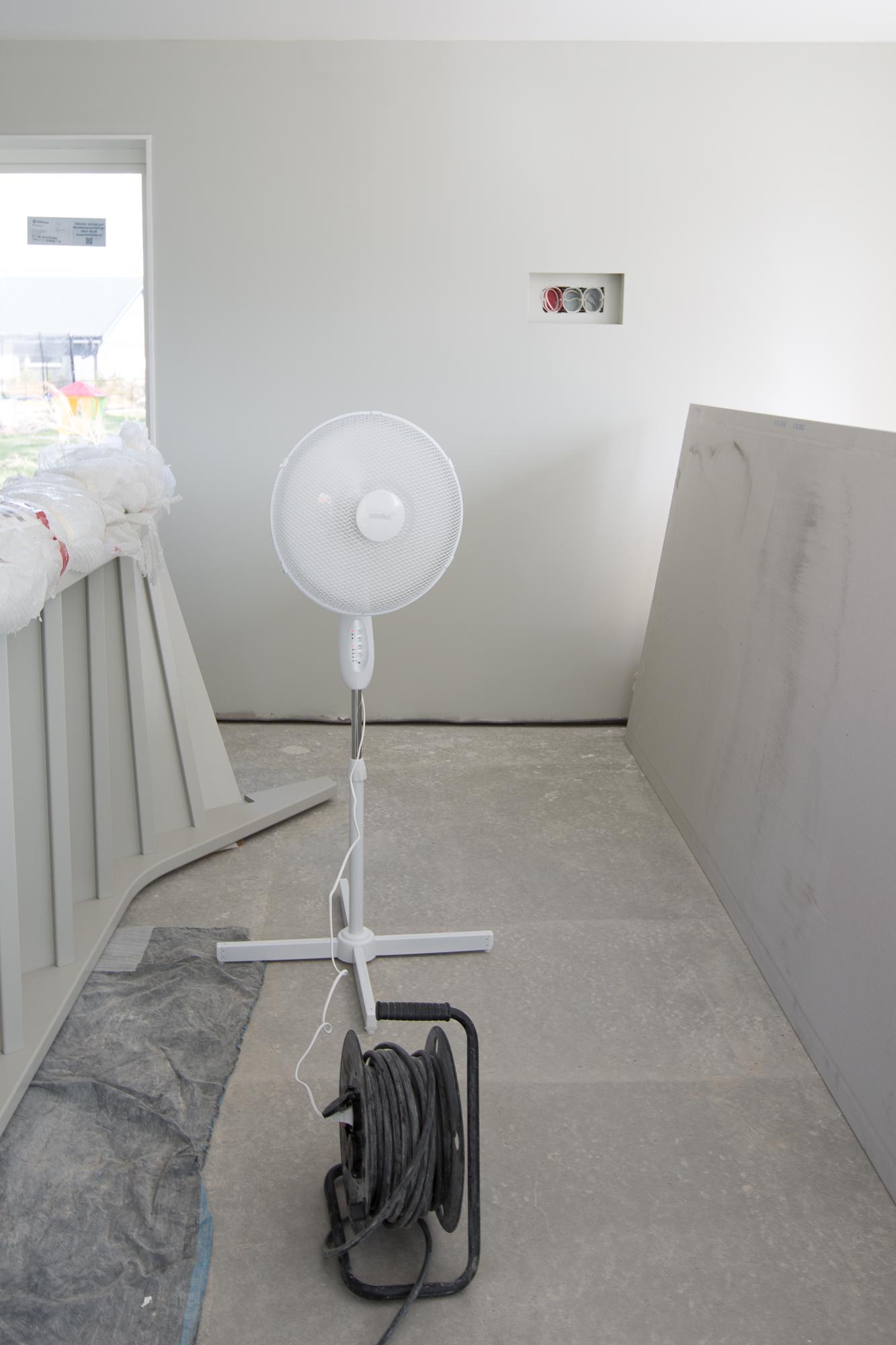 Tre fläktar får luften på nedervåningen i rörelse så den når en avfuktare.