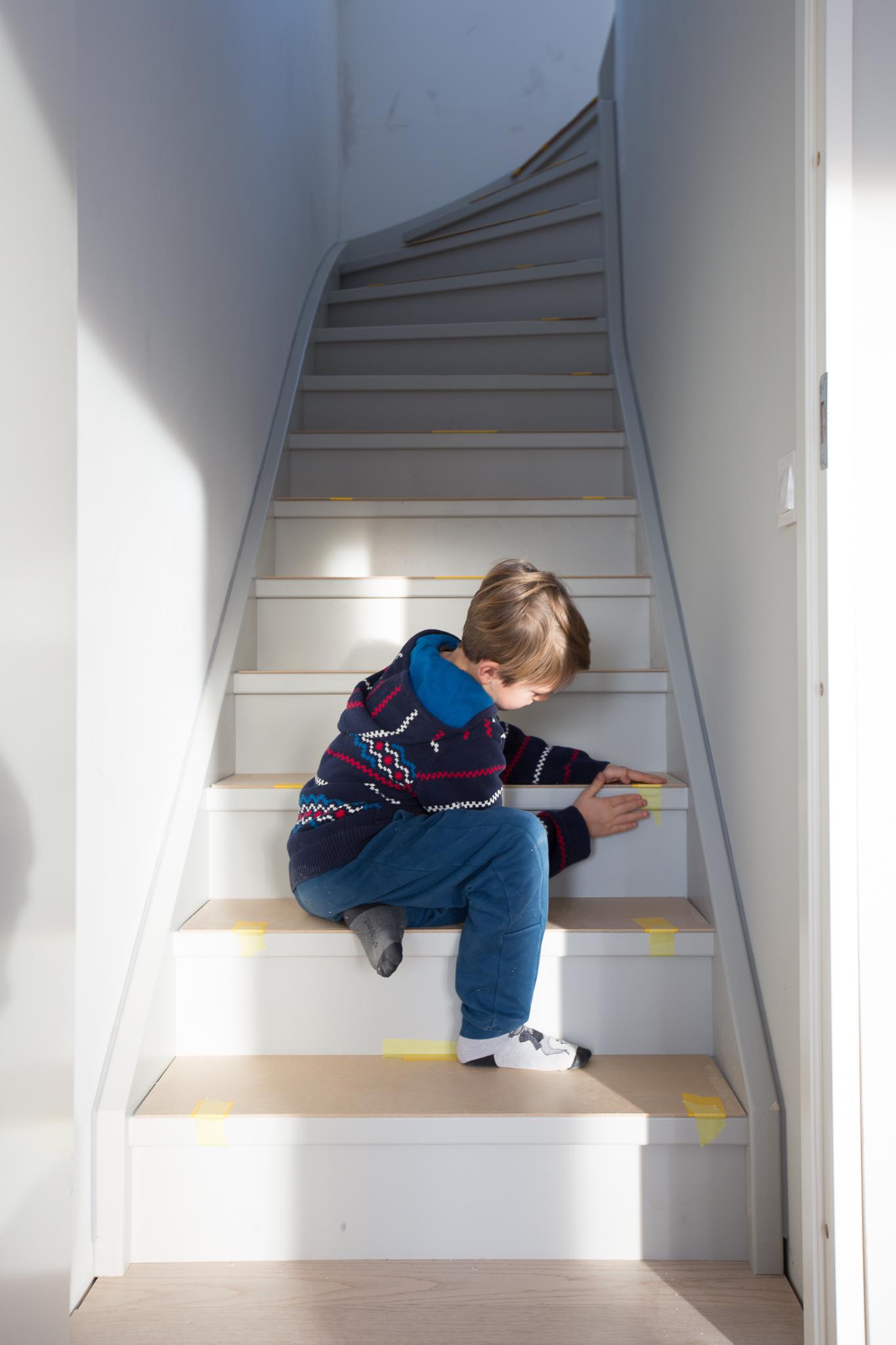 Sam hjälper till att skydda trappan inför entreprenörernas fortsatta arbete. Först masonitskivor, sen mjölkpapp.