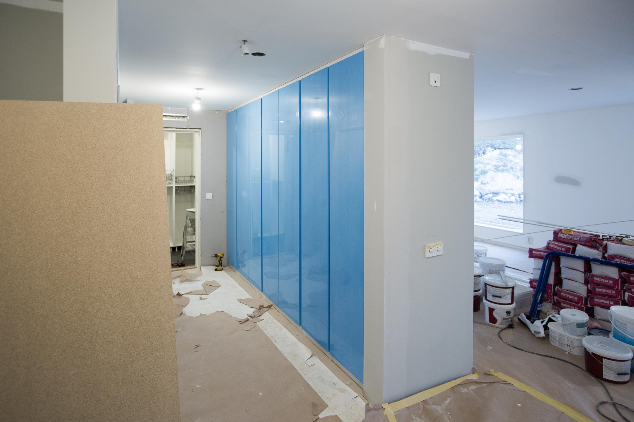 Klädförvaring och städskåp i hall. Inbyggda garderober IKEA PAX med dörr VIKANES vit (här med blåskyddsplast).Integrerade handtag i dörren så det inte finns några knoppar att fastna i.