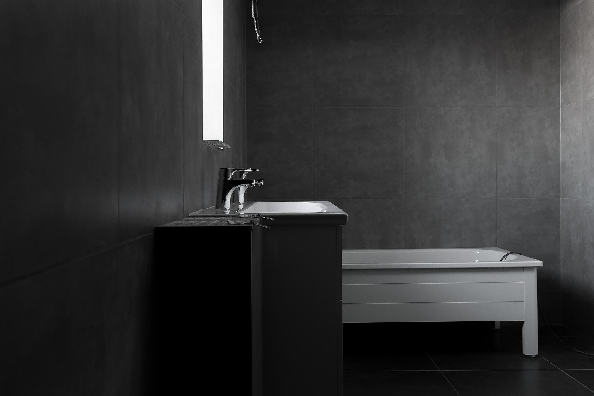Vägghängt dubbelhandfat med kommod  (Gustavsberg Artic 100).  Badkaret en klassiker i emaljerad stålplåt med halvfront av estetiska så väl som praktiska skäl  (Gustavsberg Standard) . Klinkern är från Konradssons Kakel (sponsor) och heter Cement 60x60 (grå på väggar och svart på golv).