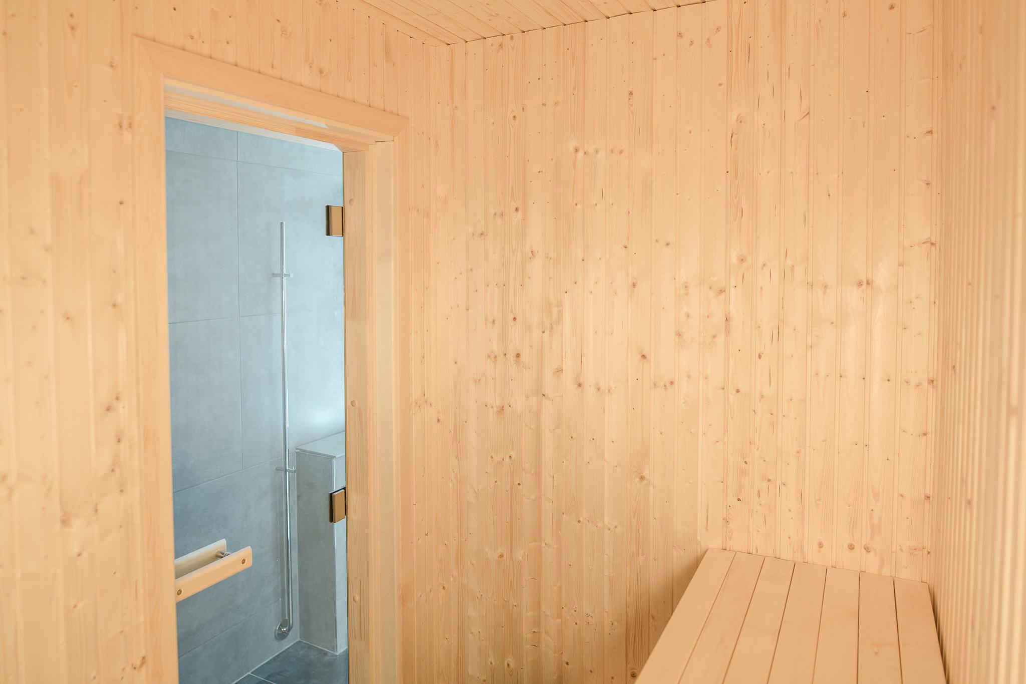 Bastun med furupanel och asplavar. Övre laven kan man flytta ner så man får en extra gästsäng. Utanför, bakom handdukstorken, syns tvättnedkastet som leder ner till en tvättkorg i tvättstugan.