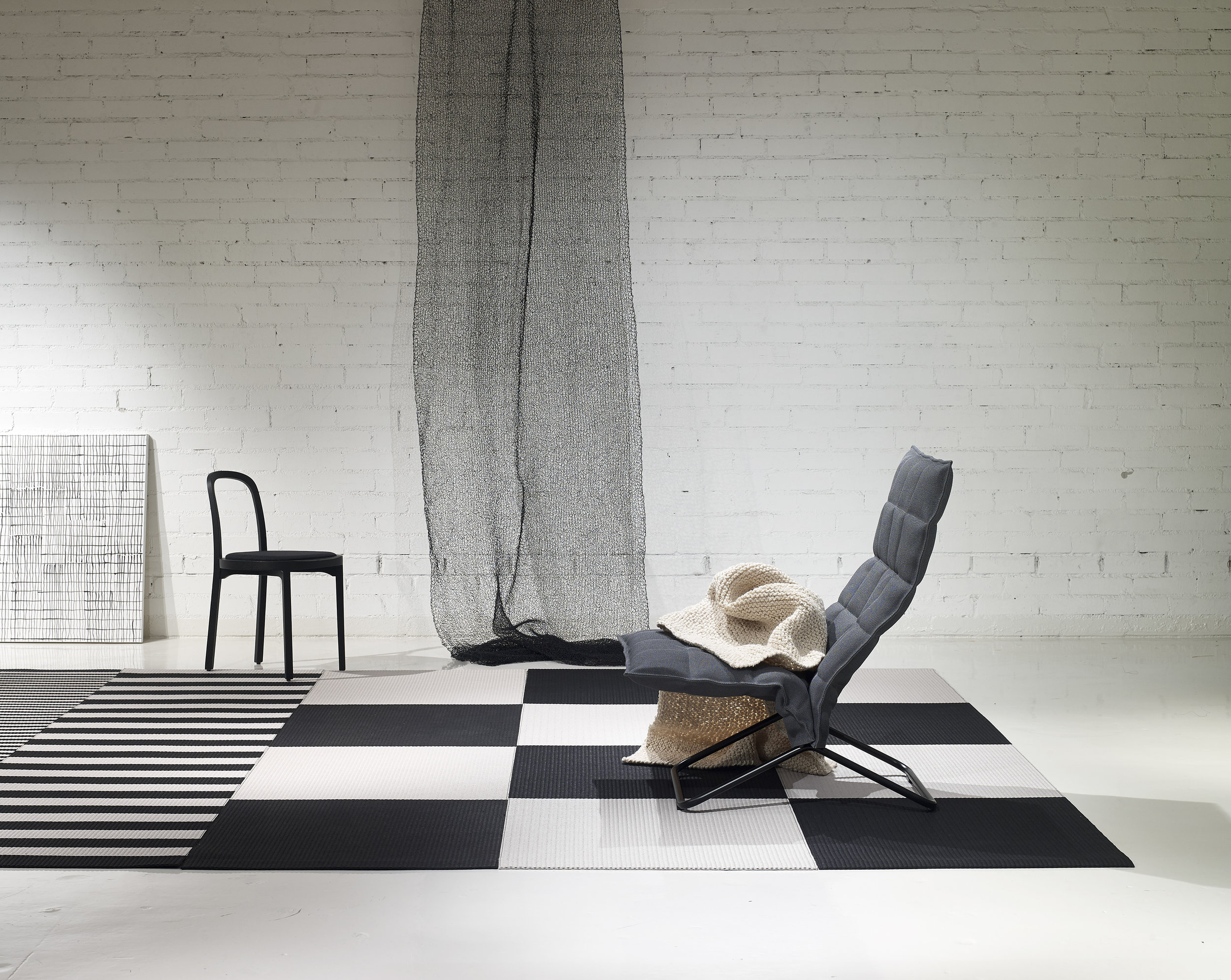 Woodnotes interior /  Squareplay  paper yarn combo with 1420915  Big Stripe  and 1190915 Stripe paper yarns black-stone, 46003  Narrow Tubular k Chair  col. graphite matt-black tubular frame, 4419 Siro+ black seat leather upholstered, 7300101 Woodwool hand knitted throw col. white and 7110902 Mesh hand knitted partition black-steel.