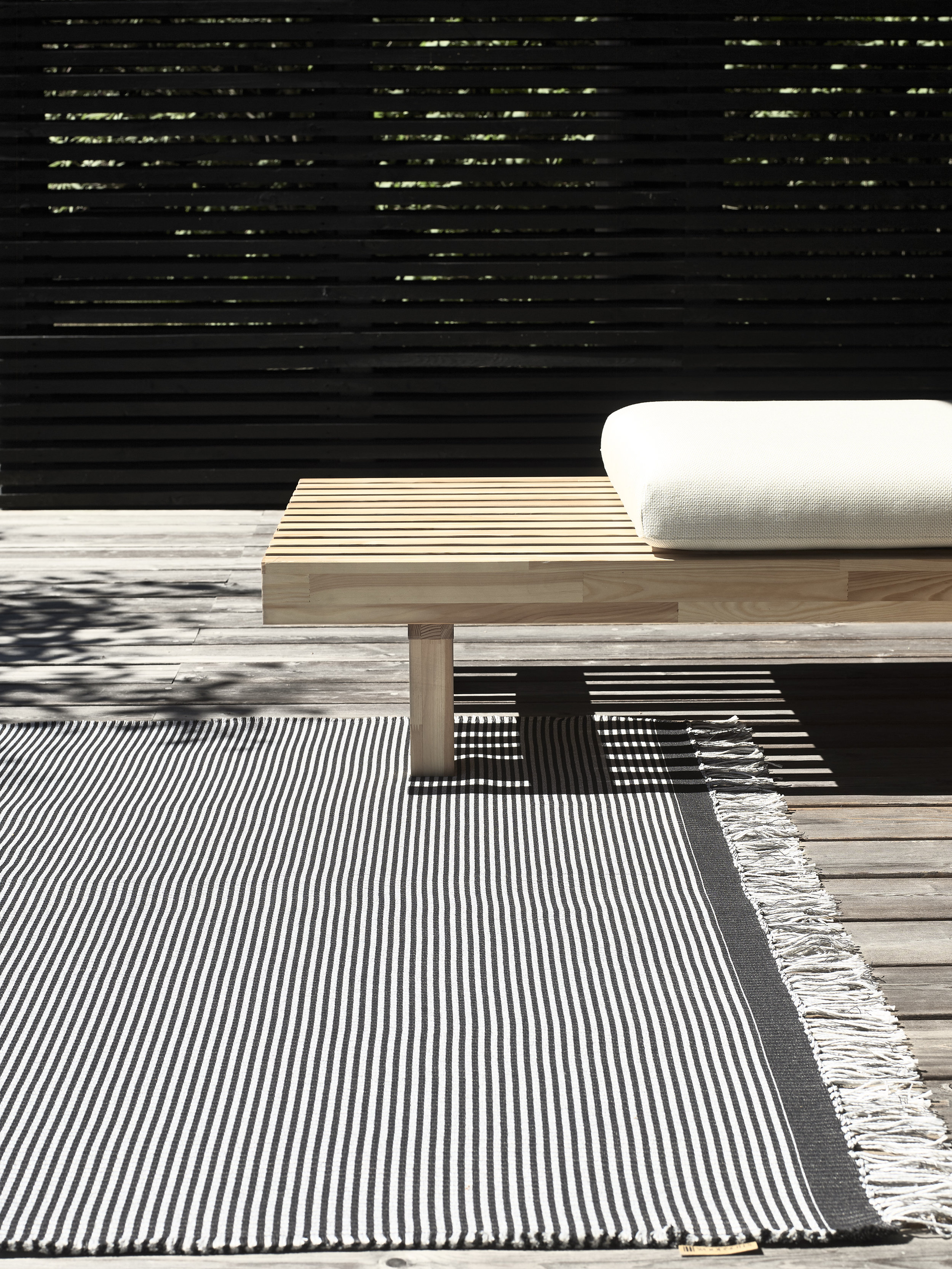 The Woodnotes outdoor carpet  has a soft feel and is transpiring therefore ideal for leisure living. Outdoor River carpet col. graphite-pearl grey.  Laveri  outdoor bench with drainable mattress upholstered Saimaa fabric col. natural white.