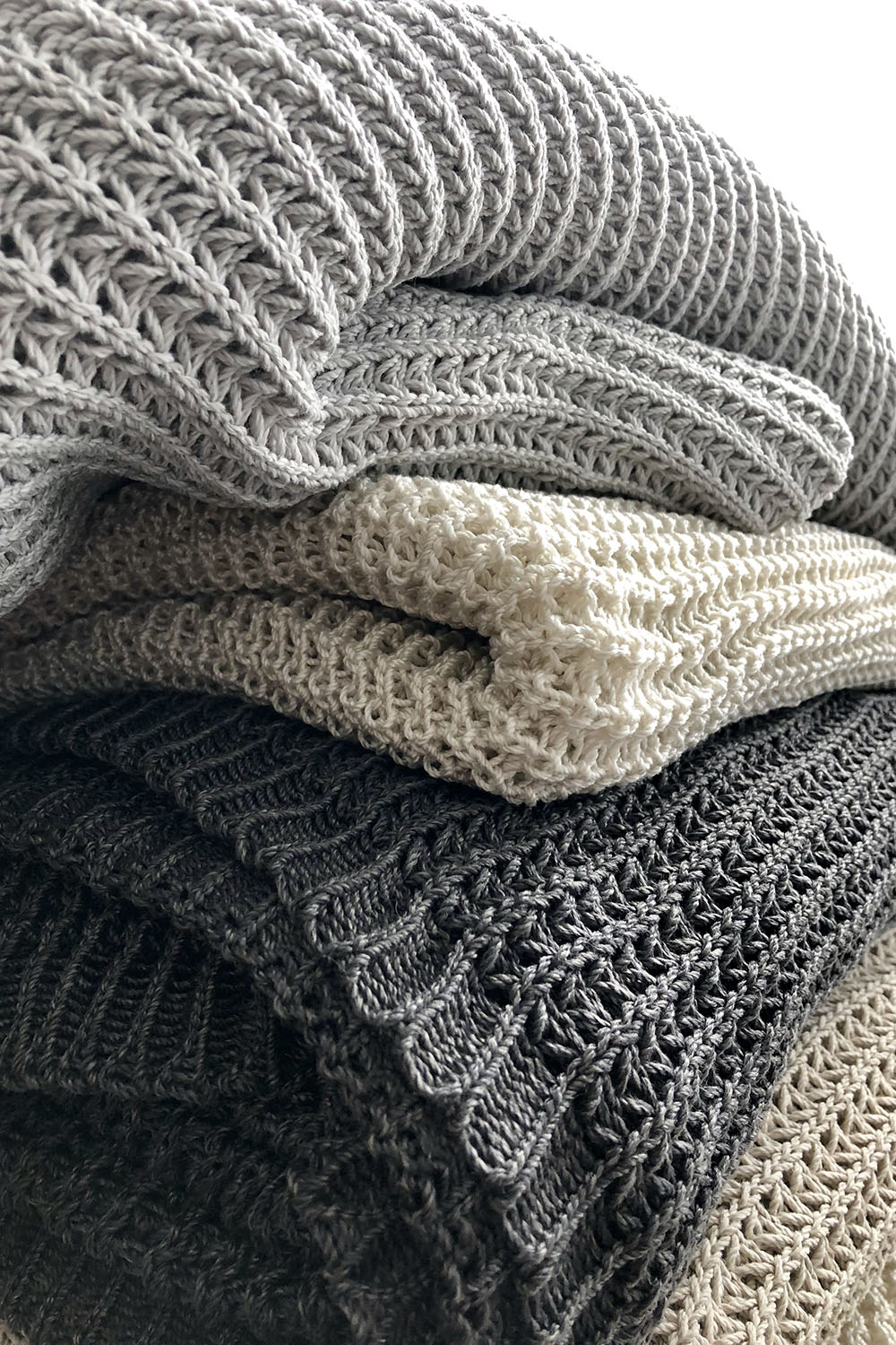 Garden throws_colour options pearl grey, natural white, graphite and light sand (from top to bottom)