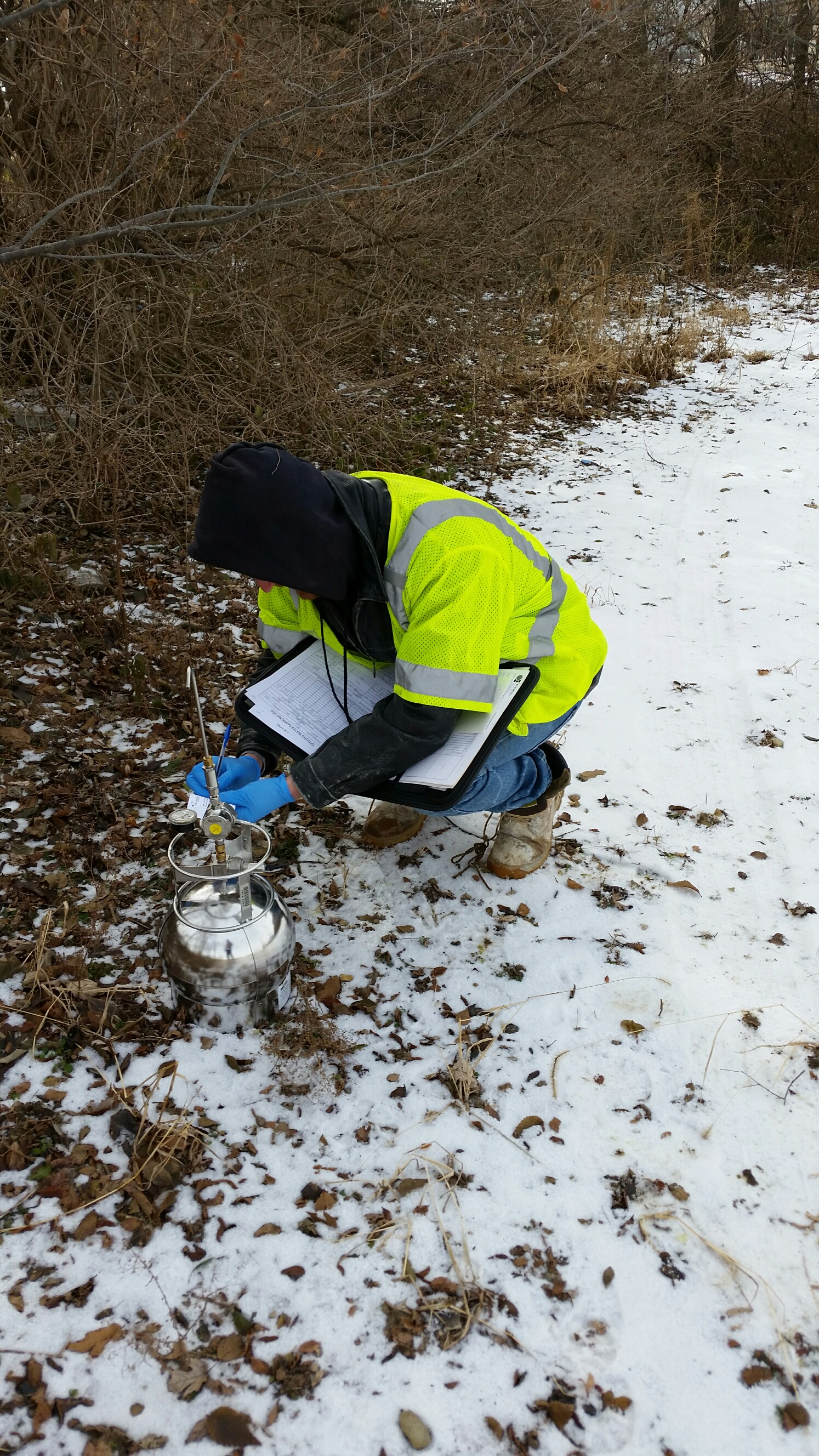 KERAMIDA staff geologist collecting an outdoor air sample using a Summa canister.