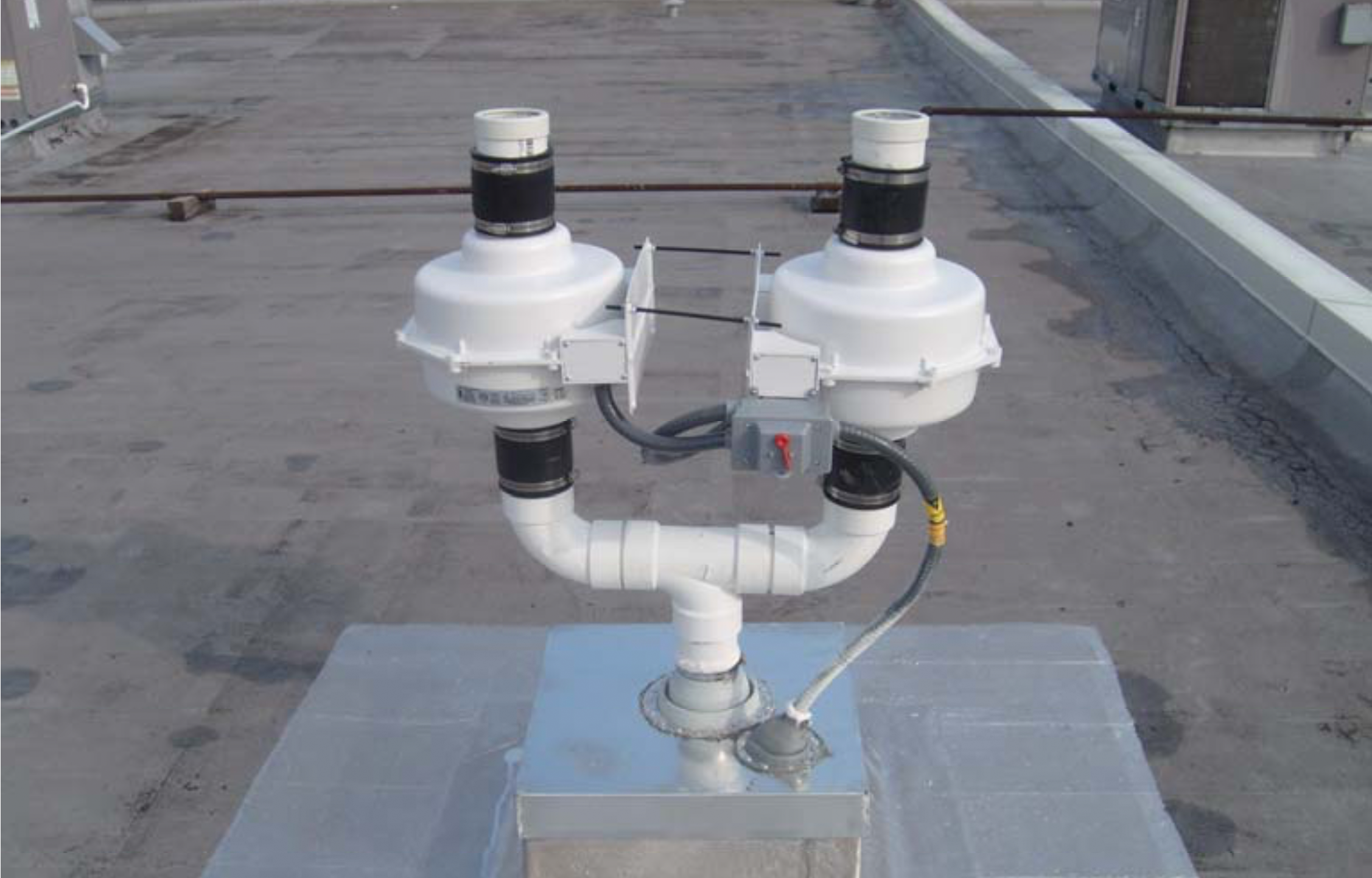 Dual-fan sub-slab vapor mitigation system installed on building roof at a commercial use building