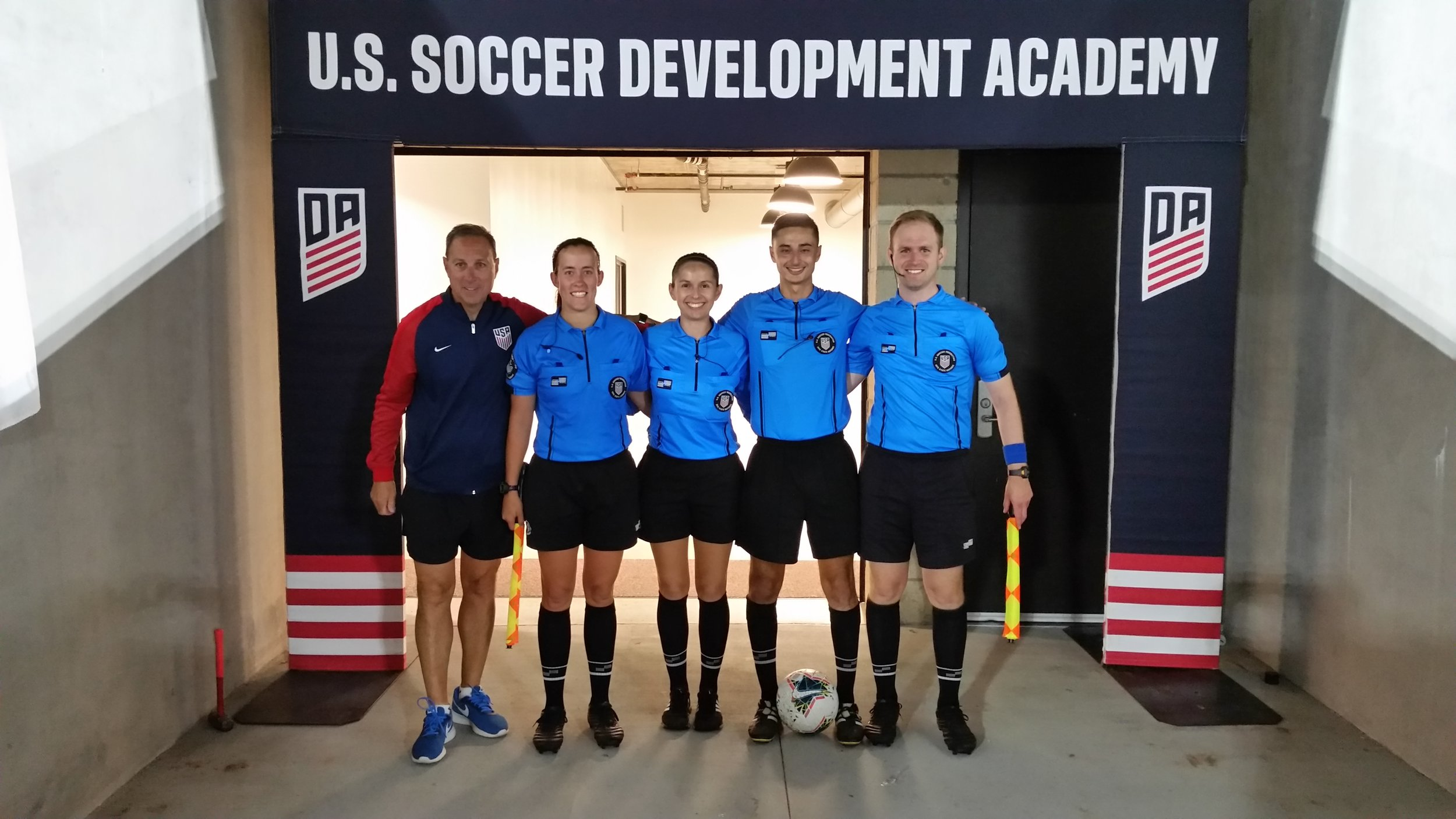 Melissa (far left referee) and crew pose with Rick Eddy, USSoccer Director of Referee Operations.