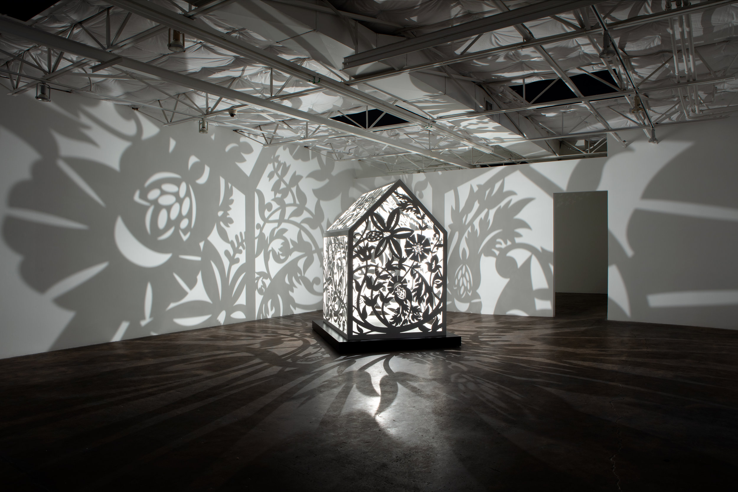 "This is NOT a Refuge! 2  Installation at Talley Dunn Gallery, Dallas, TX, 2019    Laser-cut, Resin Coated Aluminum, Light Bulb  H 93"" x W 58"" x D 72""  This is NOT a Refuge! 2 Artist Statement"