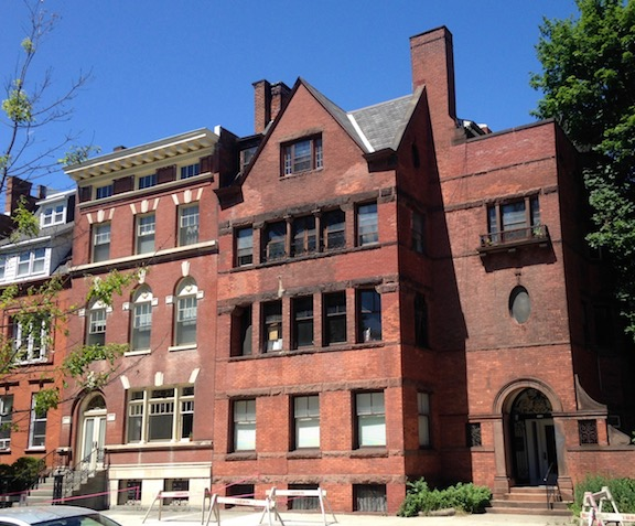 A handsome red brick colonial revival (left) next to a handsome richardsonian romanesquw