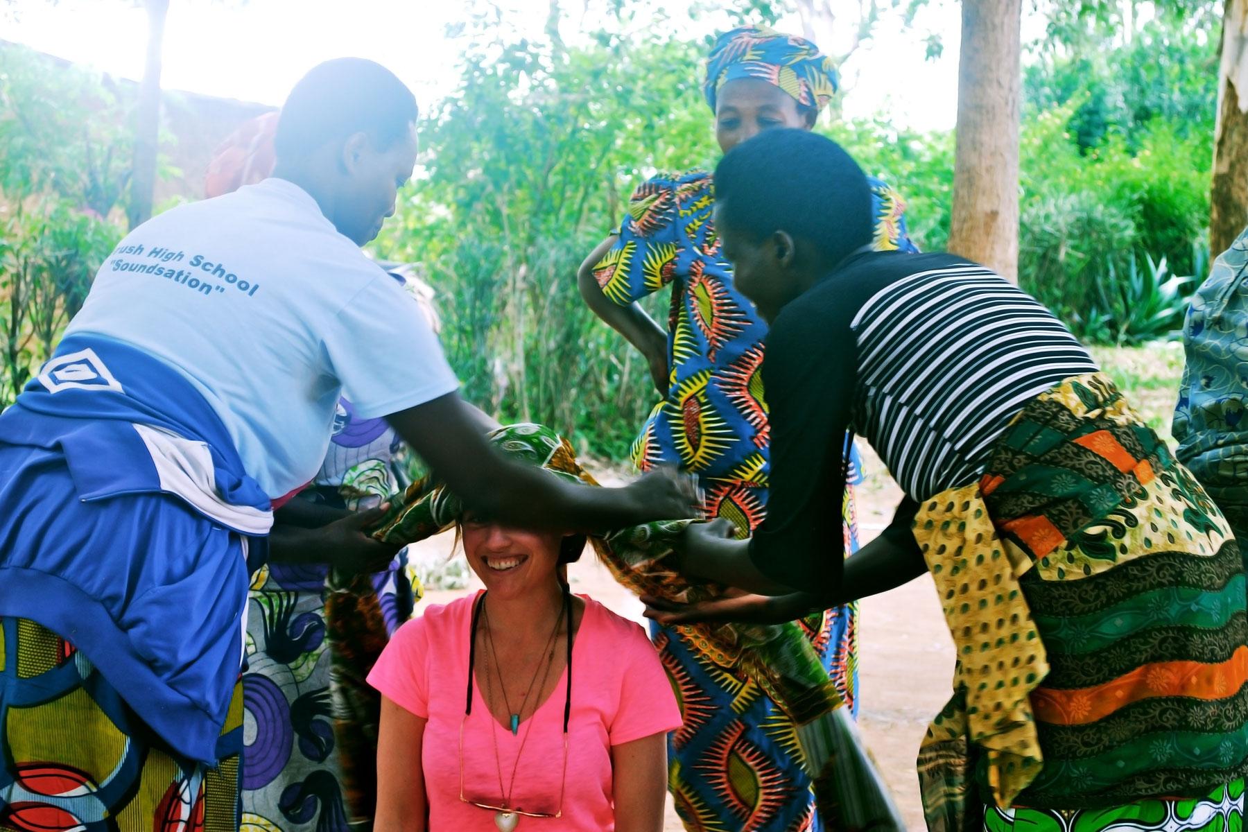 Women of Imirasire Cooperative, teaching Deirdre how to tie a head wrap.