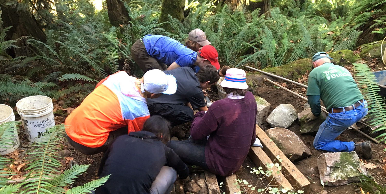 NOLS students and instructor helping build slot drains.