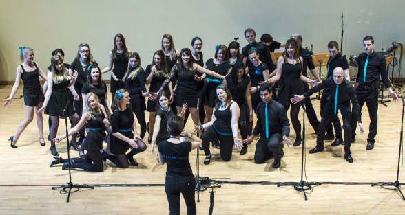 The starling singers hold a pose while emily offers direction