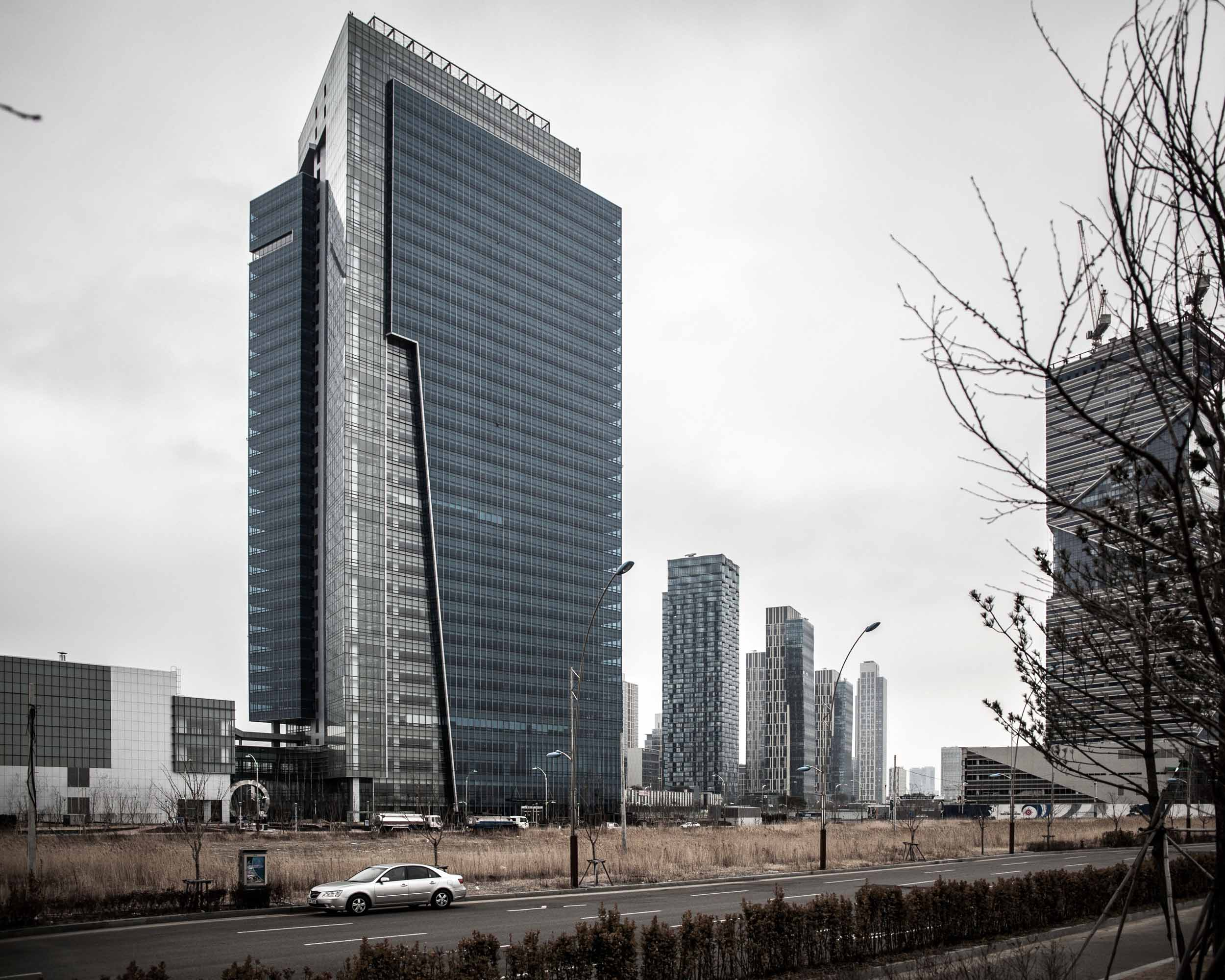 Songdo International Business District (SIBD) is a new Smart City or Ubiquitous City built from scratch on 1,500 acres of reclaimed land along Incheon's waterfront, 40 miles southwest of Seoul, South Korea and connected to Incheon International Airport by a 7.4 mile reinforced concrete highway bridge, called Incheon Bridge. Along with Yeongjong and Cheongna, it is part of the Incheon Free Economic Zone. This 10-year development project is estimated to cost in excess of $40 billion, making it one of the most expensive development projects ever undertaken and it is the largest private real estate development in history. By its completion date in 2015, the district is planned to contain 80,000 apartments, 50,000,000 square feet of office space and 10,000,000 square feet of retail space. The 65-floor Northeast Asia Trade Tower became South Korea's tallest building. The plan was designed by the New York office of Kohn Pedersen Fox (KPF).