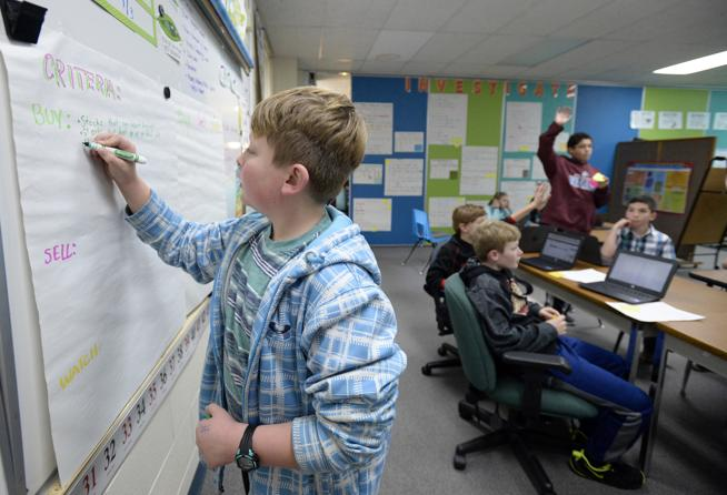 Carrie Martin Elementary School fifth-grader Josiah Crill, 10, writes reasons to buy stock on the board during gifted and talented class Thursday, Dec. 6, 2018, at the school in Loveland. During a unit on the stock market, the students learned how to research and trade stocks as a virtual lesson. Three students won first and second place against students across the state by earning the most growth in their portfolios. Josiah is one of the students who won first place ( Jenny Sparks / Loveland Reporter-Herald )