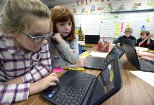 Celia Davis, 9, left, and Aidan Coble, 9, center, Carrie Martin Elementary School fourth-graders, check out their stock on a computer during gifted and talented class Thursday, Dec. 6, 2018, at the school in Loveland. During a unit on the stock market, the students learned how to research and trade stocks as a virtual lesson. Three kids in the class won first and second place against students across the state by earning the most growth in their portfolios. Aidan is one of the students who won second place. ( Jenny Sparks / Loveland Reporter-Herald )