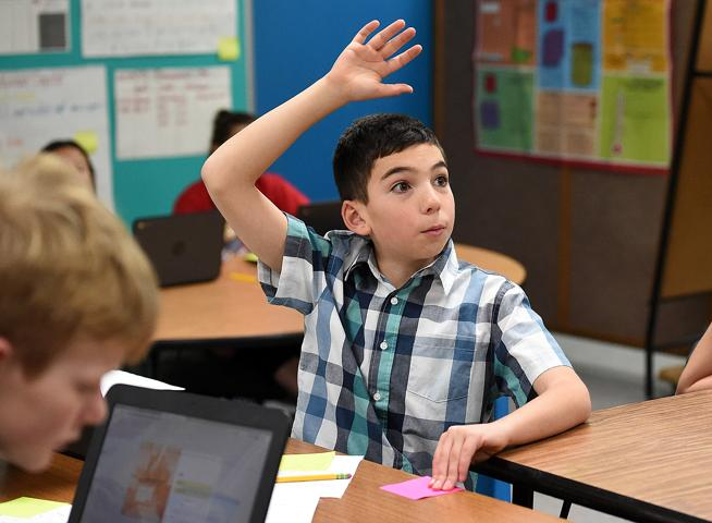 Carrie Martin Elementary School Bradyn Cronin, 10, raises his hand to answer a question about the stock market during gifted and talented class Thursday, Dec. 6, 2018, at the school in Loveland. During a unit on the stock market, the students learned how to research and trade stocks as a virtual lesson. Three kids in the class won first and second place against students across the state by earning the most growth in their portfolios. Bradyn is one of the students who won first place ( Jenny Sparks / Loveland Reporter-Herald )