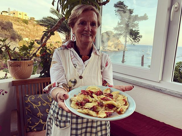 Giovanna presenting her finished ravioli dressed with a sauce made from prawn heads (the prawns are the main course). The eggs to make her pasta come from her chickens, who surely have a coop with the best view in the world (see second pic). No photo of the chooks cos they were surrounded by a film crew. 😊 #pastagrannies #ravioli #ischia