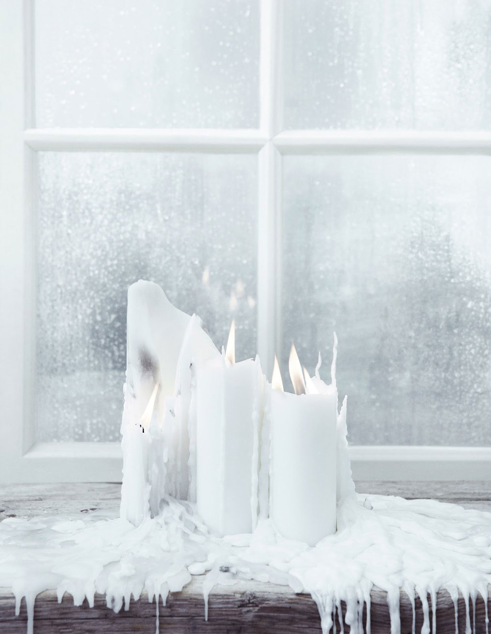 Cluster dripping white candles for a haunted ambience (via Visual Optimism)