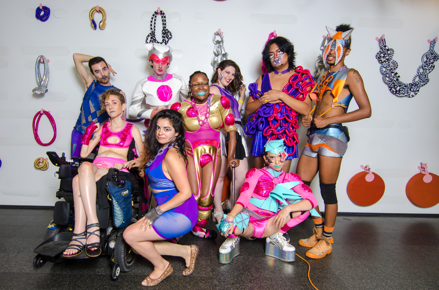 Photo by Colectivo Multipolar of The Radical Visibility Collective at The Museum of Contemporary Art in Chicago. From left to right: Gabriel Anaya in blue and silver vinyl and chainmaille armor, Carrie K in all pink with a hand brace cover, crop top with chest hole and shorts, Vogds in white vinyl and pink crop top and matching helmet with a chainmaille choker, Michelle Zacarias in a blue and purple halter crop and miniskirt, Miss Alexis La'Shay Smith in a gold and pink crop top and holey singlet with muscle poufs, Nina Litoff in a purple bodysuit and black/ holo circle skirt, Sky Cubacub in pink spandex with geometric aqua vinyl headpiece, spikey crop top and leg armor, Ubae in a purple skirted one piece bathing suit and soft sculpture shawl in pink and purple and Compton Q in grey, orange and blue shorts, crop top and horned mask headpiece.