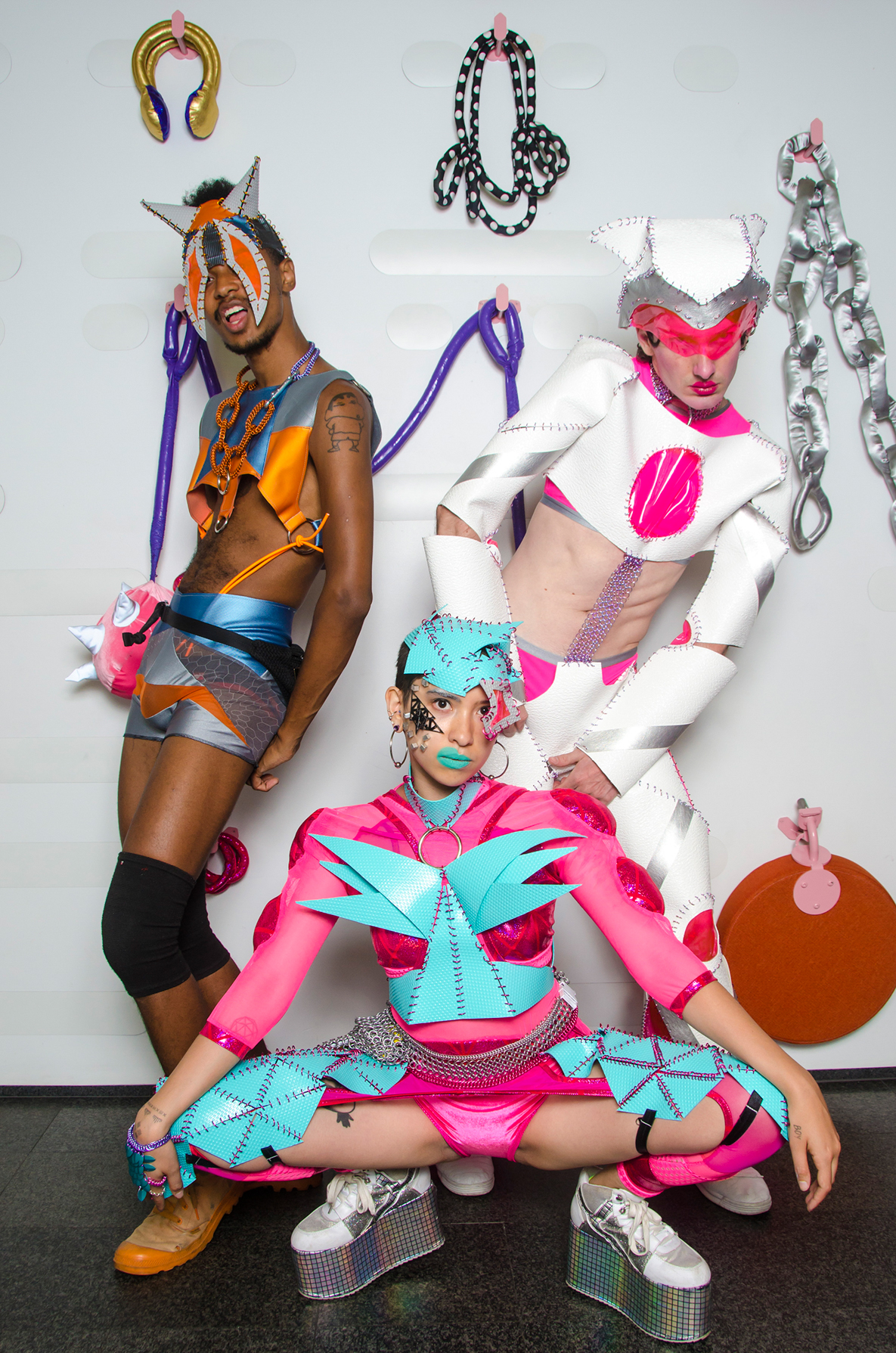 Photo by Colectivo Multipolar  3 NeuroQueers posed in a triangle, Compton is wearing grey, orange and blue vinyl crop top and shorts with large O rings that have orange rope attachments, a metamaille necklace and horned headpiece with spikey eyes! Vogds is wearing white with pink details vinyl outfit that is chainmailled together with a vinyl helmet that has cute ears! sky is wearing pink spandex muscle arms alien crop with aqua vinyl spikey crop top, headpiece and leg pieces!