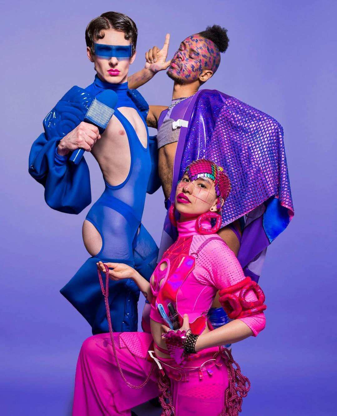 Photo by Colectivo Multipolar  Sky, Jake, and Compton all posing against a purple background . Sky is wearing pink pants, crop top, soft sculpture, and scalemaille hand piece and head piece. Jake is wearing a blue jumpsuit with poofy sleeves and legs and cut-outs at the chest and butt, with a blue microphone and visor. Compton is wearing a purple crop top, leggings, and cape and wearing a face full of pink and blue brush strokes.