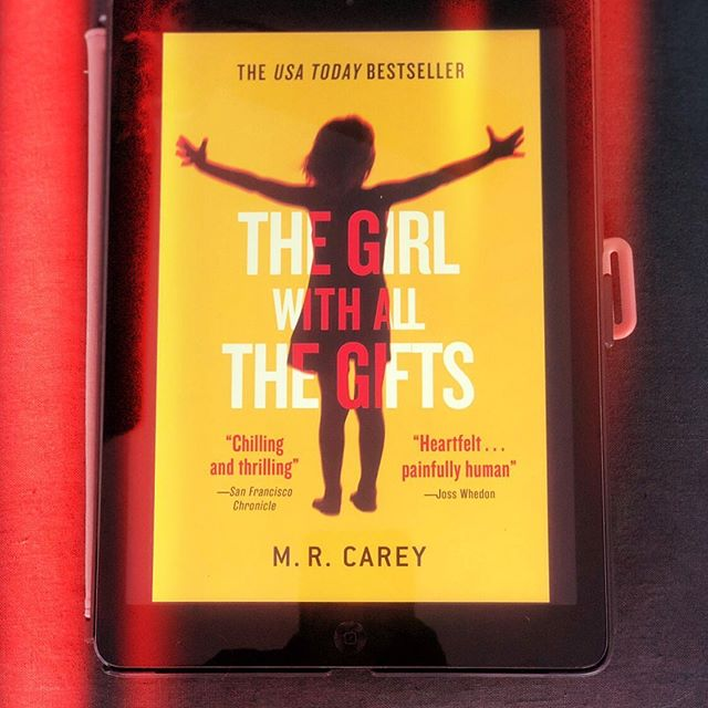 """We read """"The Girl With All the Gifts"""" by M.R. Carey this past month for book club. We branched out from our historical fiction genre and tried Sci-Fi! Not just any type of science fiction, though. Zombies 🧟♂️ 🧟♀️ !!! Yes, we read about zombies, but it wasn't your typical zombie story. Ironically enough, it was more """"human"""" than that. The book's over-arching themes consisted of the nature of human survival,  the quest for knowledge and power, and understanding and accepting diversity.  The movie adaptation staring Glenn Close hit theaters in 2017. You can now find it on @amazonprimevideo . Of course, I read the book and watched the movie and found the book to be more compelling. Surprise, Surprise. The movie took some liberties with the story that I feel changed the mood a bit. Click the link in my bio to read my review & to see which book we've selected next.  Join us on our book-reading journey! Each month I'll post our next book pick and a review of the previous so that you can follow along and we can create a virtual book club together. 📚 Have you read """"The Girl With All the Gifts""""? What were your thoughts? ********** #thegirlwithallthegifts #mrcarey #scifi #sciencefiction #zombies #theendoftheworldasweknowit #bookclubcentral#booklover #bookclubofinstagram#bookshelf #bookstagram#bookreview #virtualbookclub #ilikebigbooksandicannotlie #livelaughlighty#satxbloggers #satxblogger"""