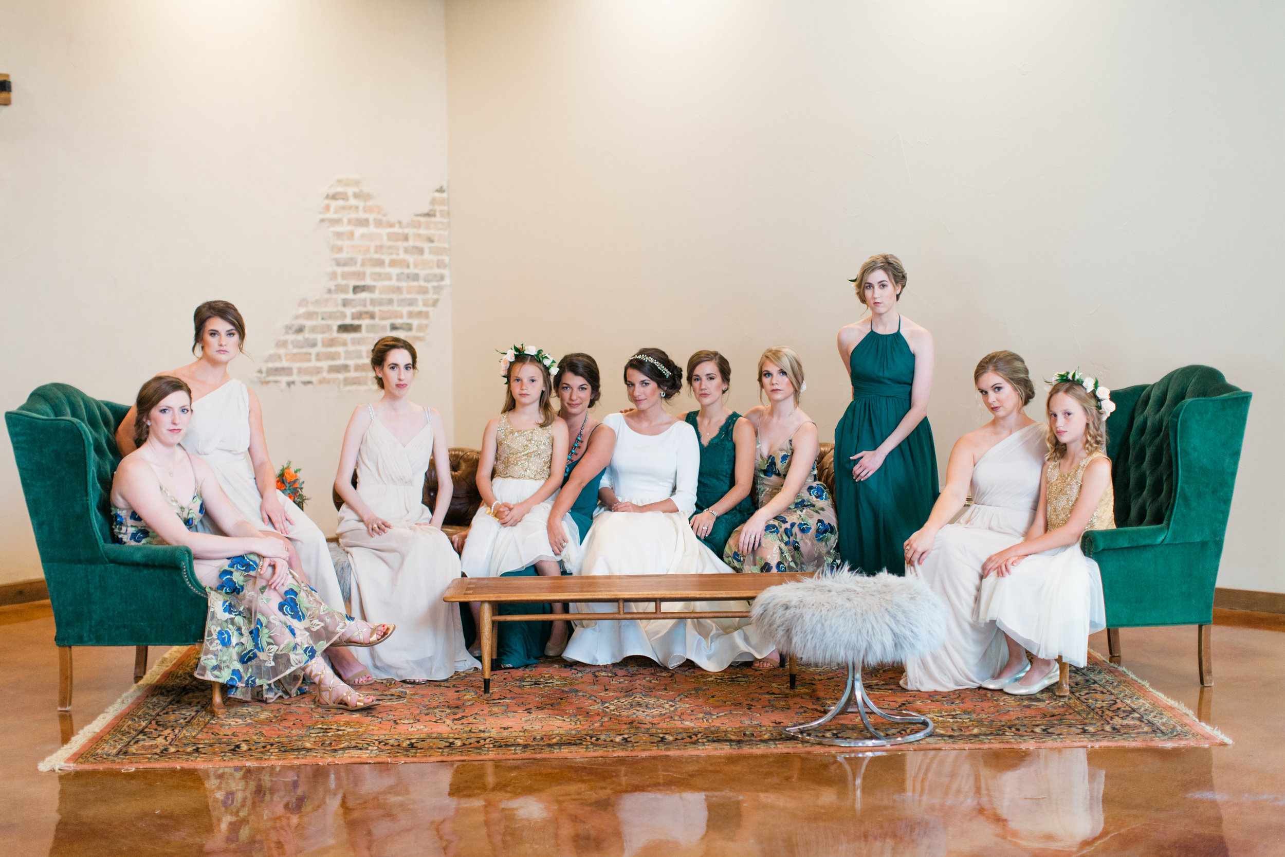 Our lounge is the perfect backdrop for this beautiful bridal party photo. The emerald green tufted chairs and the bridesmaid dresses, seriously!