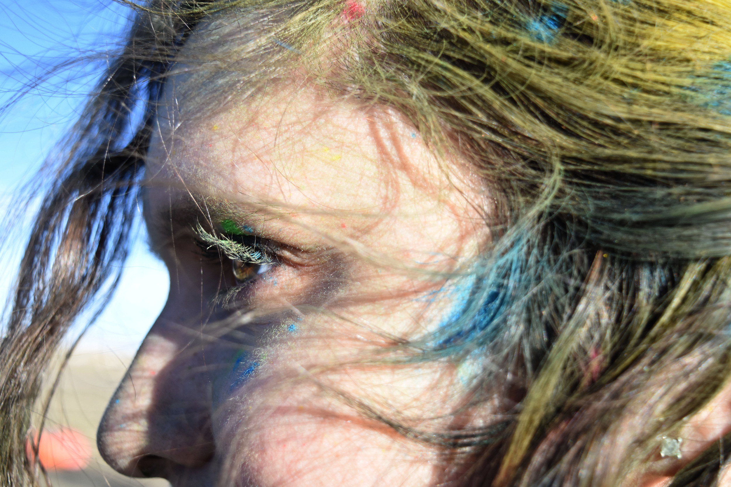 Senior Kelsey Pharis face is painted multicolor as she looks toward the rest of the student body in attendance at the color fight.