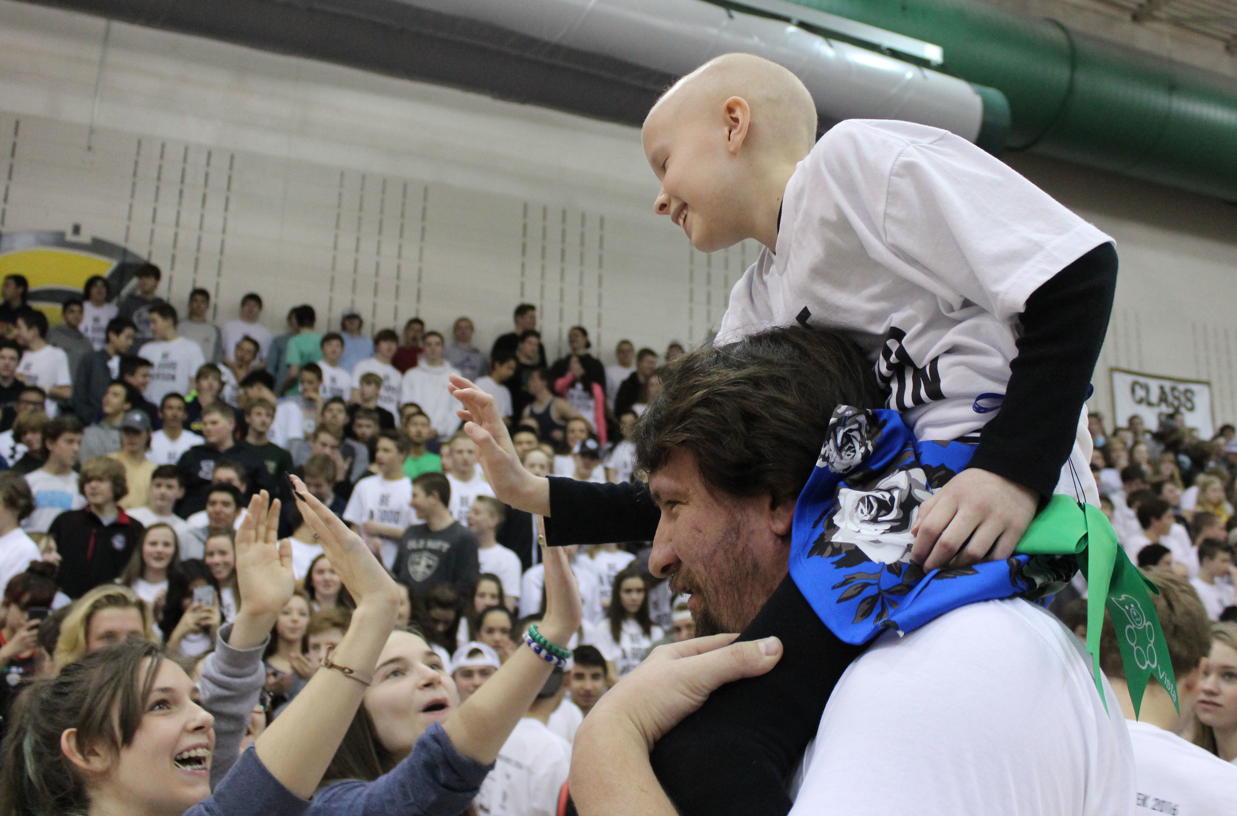 Marlee, the Wish Kid at Mountain Vista High School, rides around the main gym on math teacher Bob Wood's shoulders during the closing assembly. The assembly was the first time the majority of Mountain Vista students had actually seen the child that they raised nearly $100,000 for.
