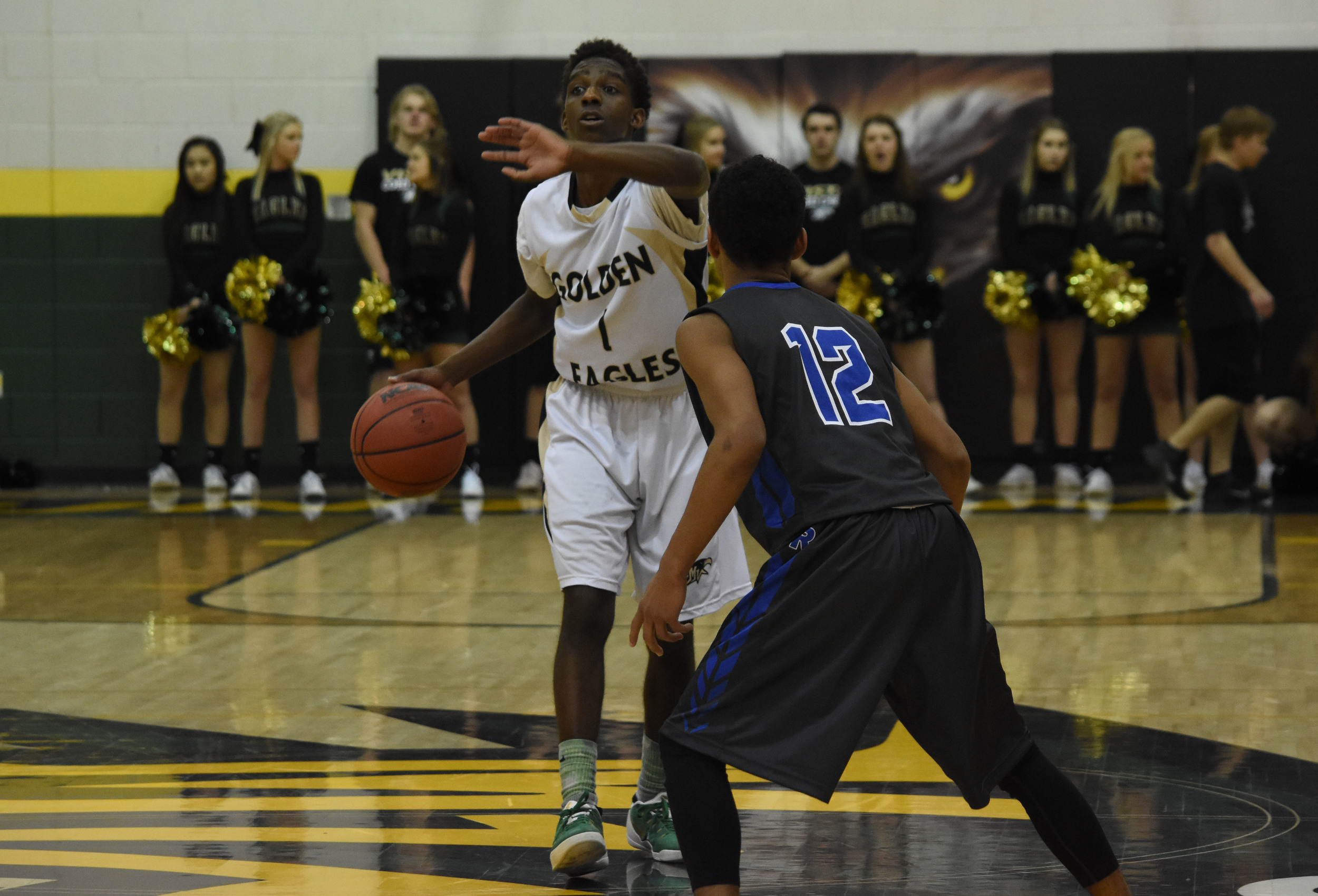 Junior Isaac Essien yells down the court at his teammates to set up a shot.
