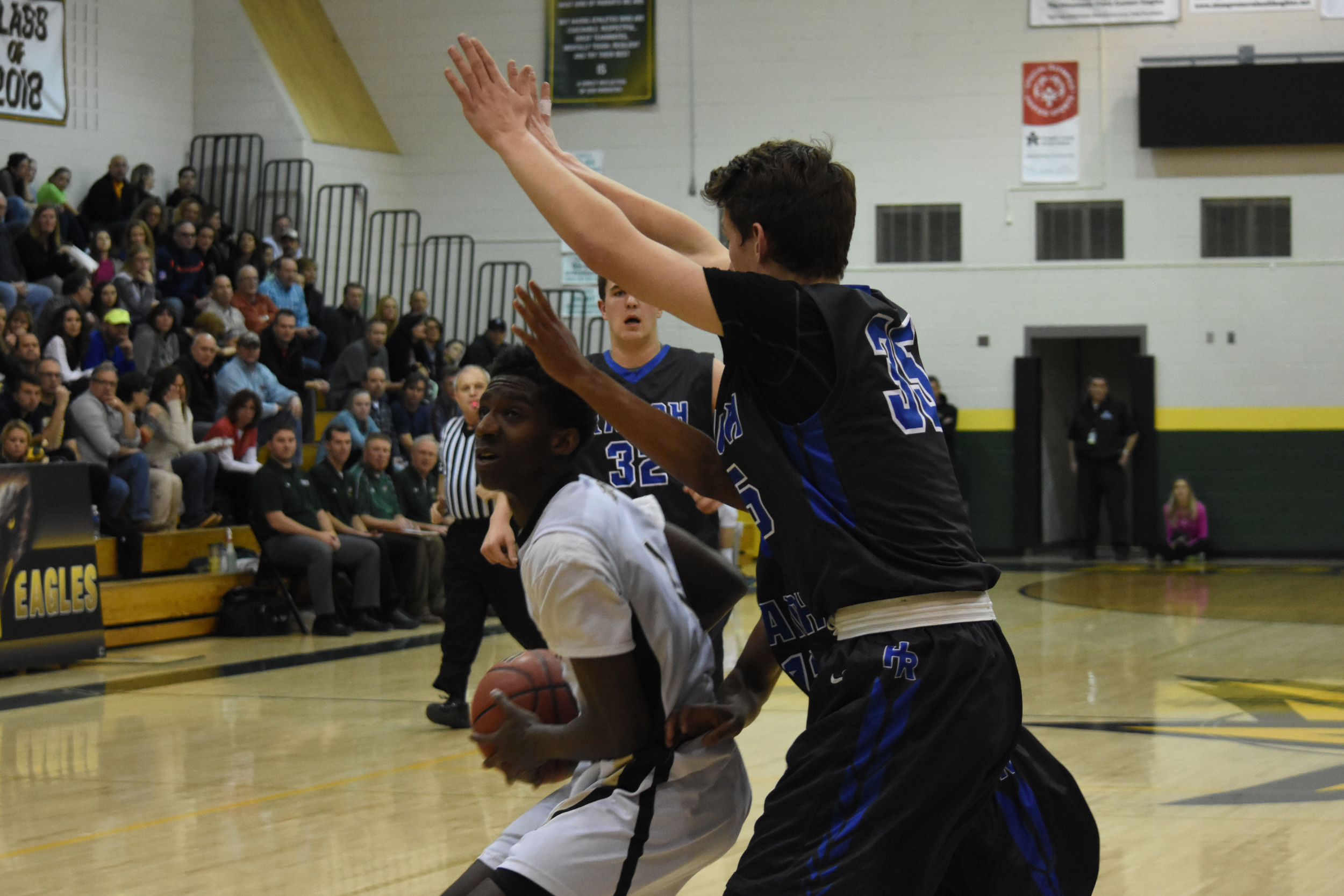 Junior Isaac Essien looks to shoot two with a towering Highlands Ranch defender hunched overhead.