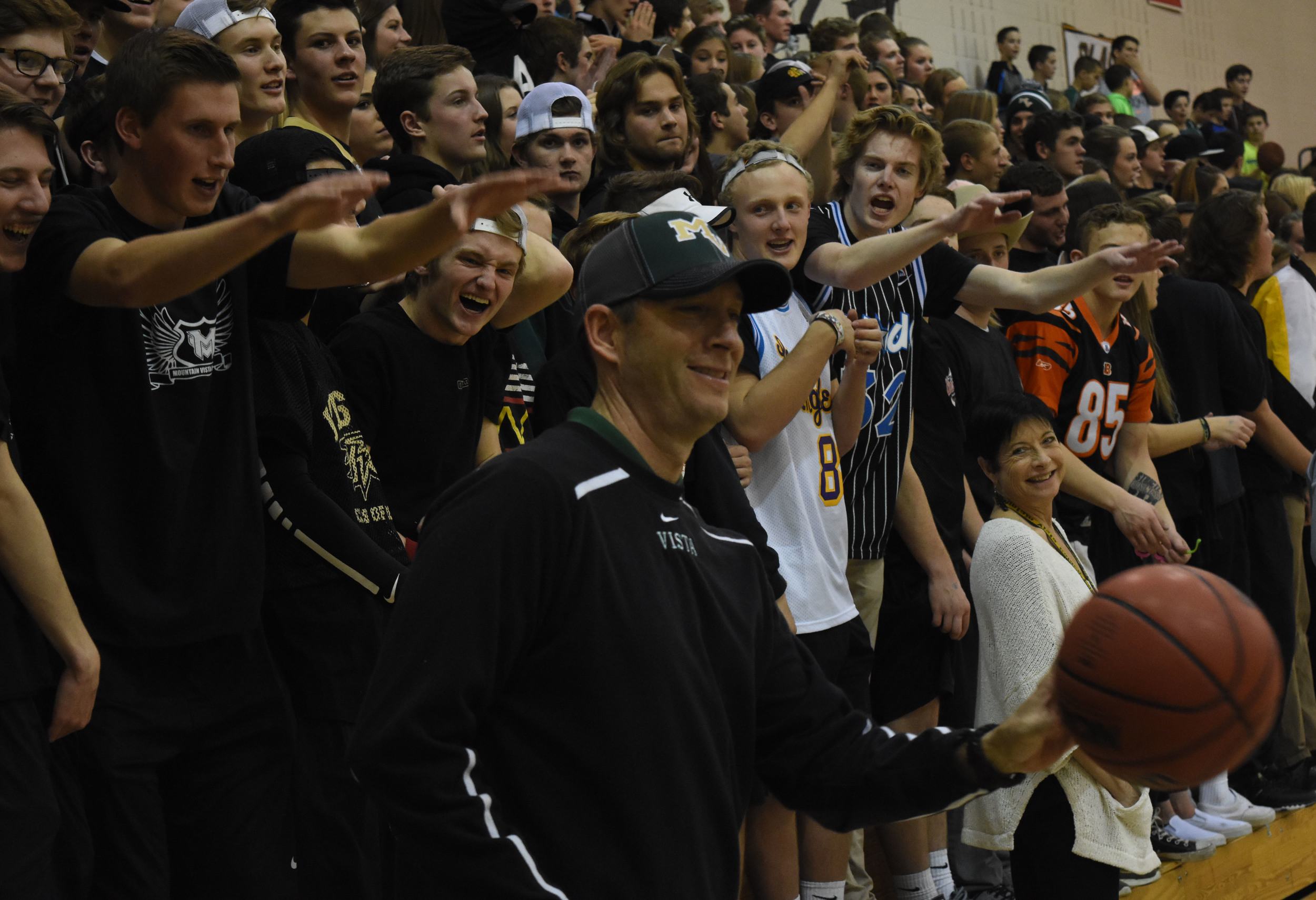 Principal Michael Weaver tosses a ball back to the court while the MV Unit gets hype.