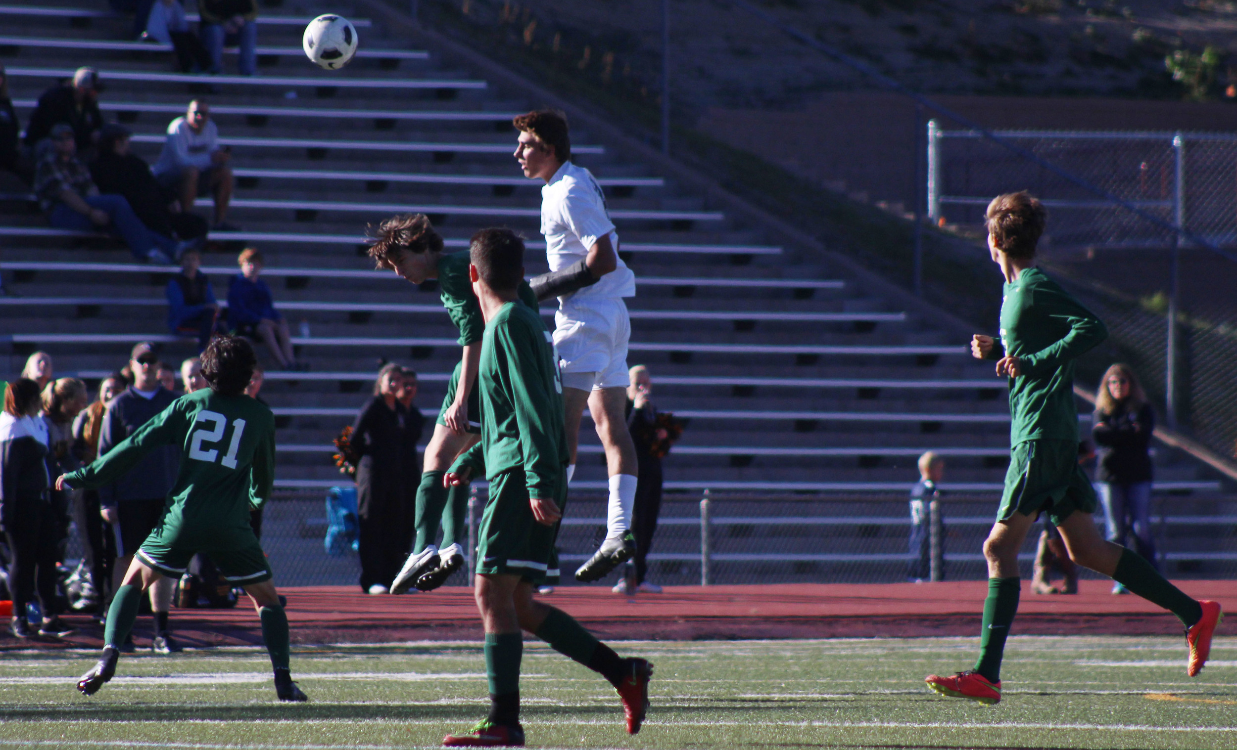 Senior Matias Grossi and an Arapahoe player head a ball into Vista territory.