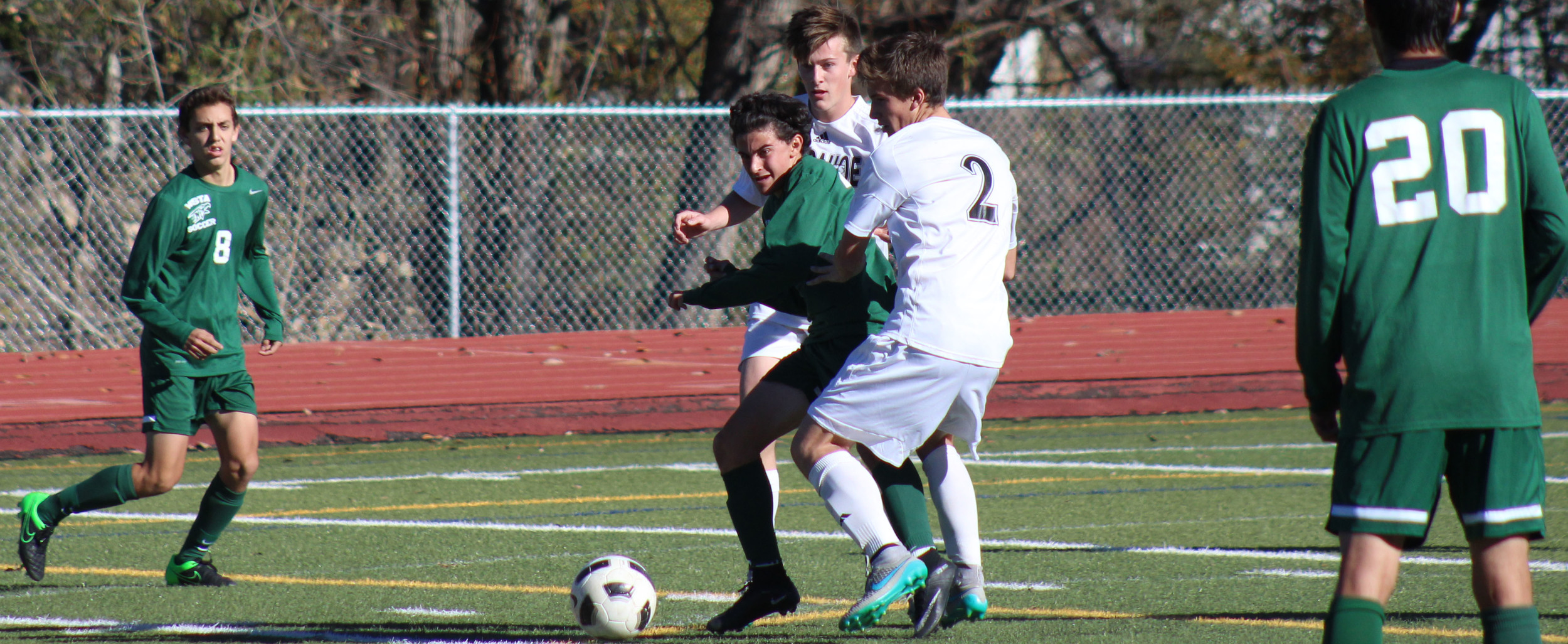 Junior Chase Pacheco dribbles a ball between two Arapahoe defenders during the Great Eight playoff game.