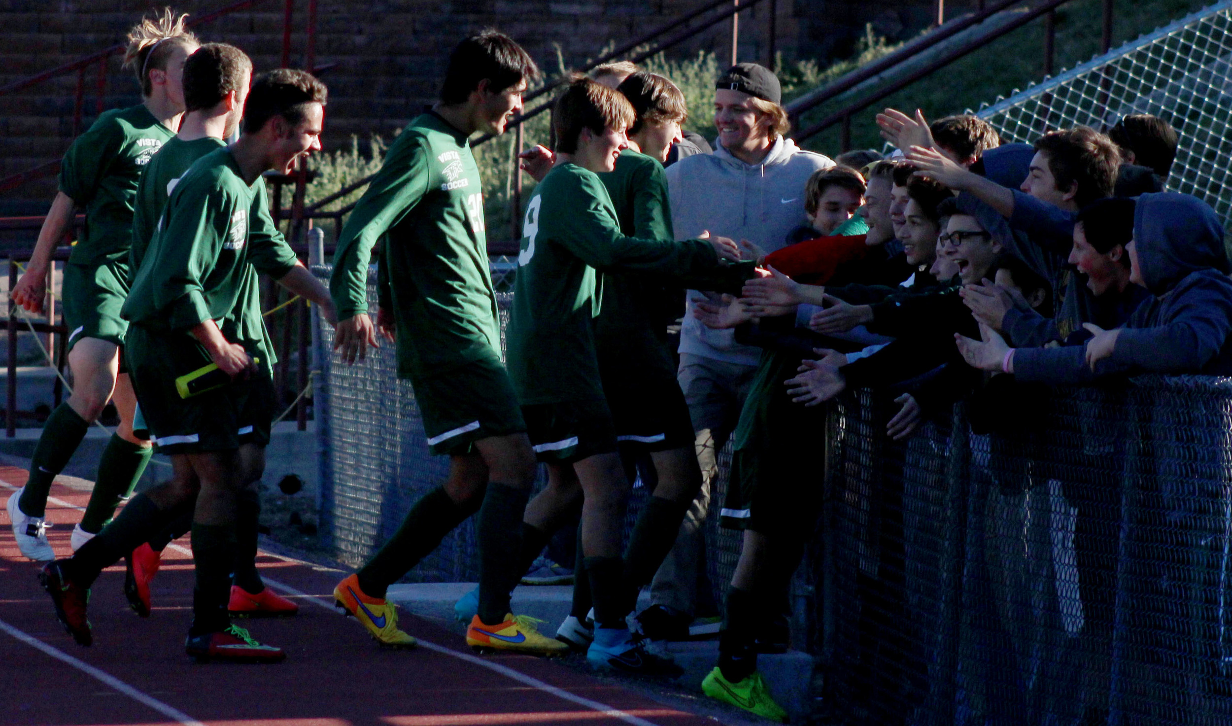 The varsity soccer team rushes the fence after defeating Arapahoe, 2-1, to advance to the final four.