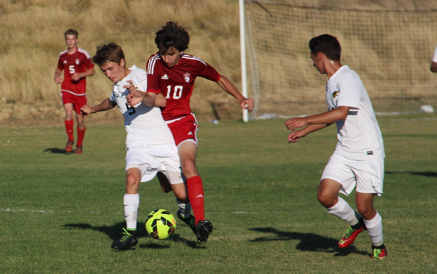 Senior Brent Lackey dribbles the ball around a defender from Heritage High School.