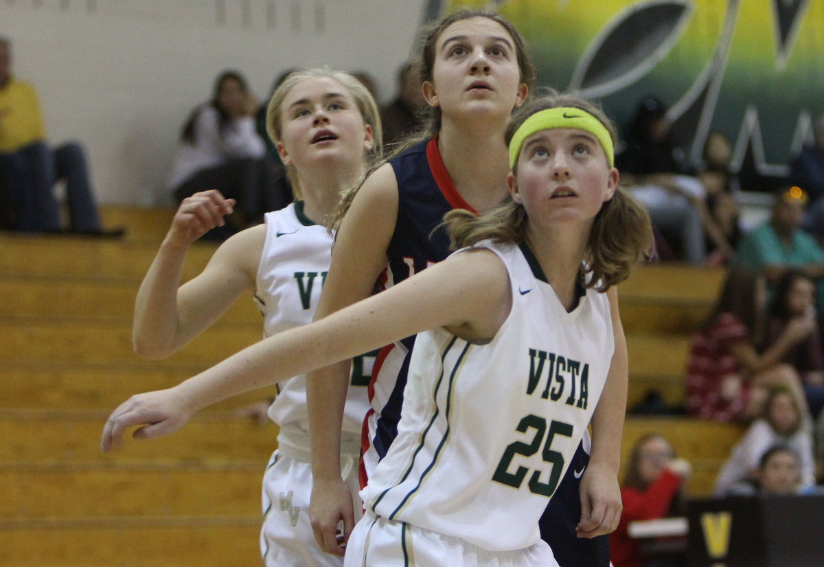 Kyla Dezell (front) and Abby Walz (back) look to snag a rebound following a free throw during a game against Liberty High School. Dezell, Walz and the rest of the Golden Eagles defeated Liberty, 68-46.
