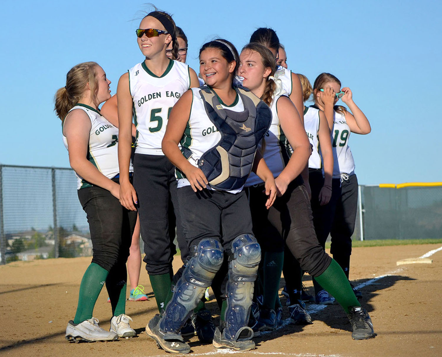 The level-three softball team excitedly gathers together before saying farewell to Douglas County after their win.