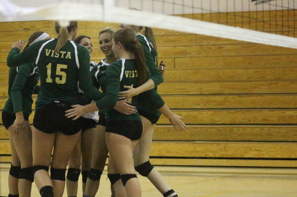 After serving an ace, the JV volleyball team congregates for a quick celebration.