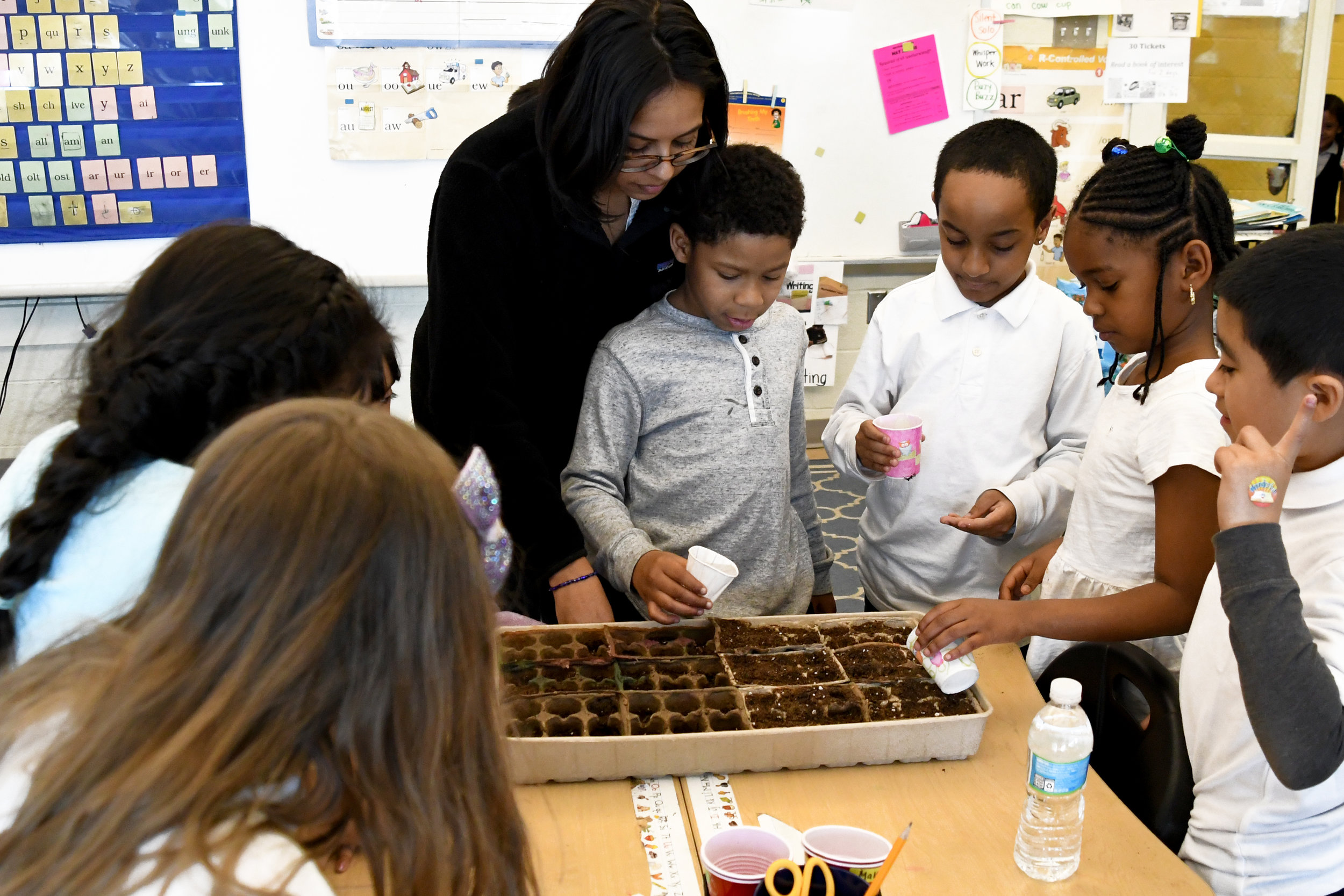 Students water their newly-planted flowers at Seaton Elementary with the help of Nikhita Jain.